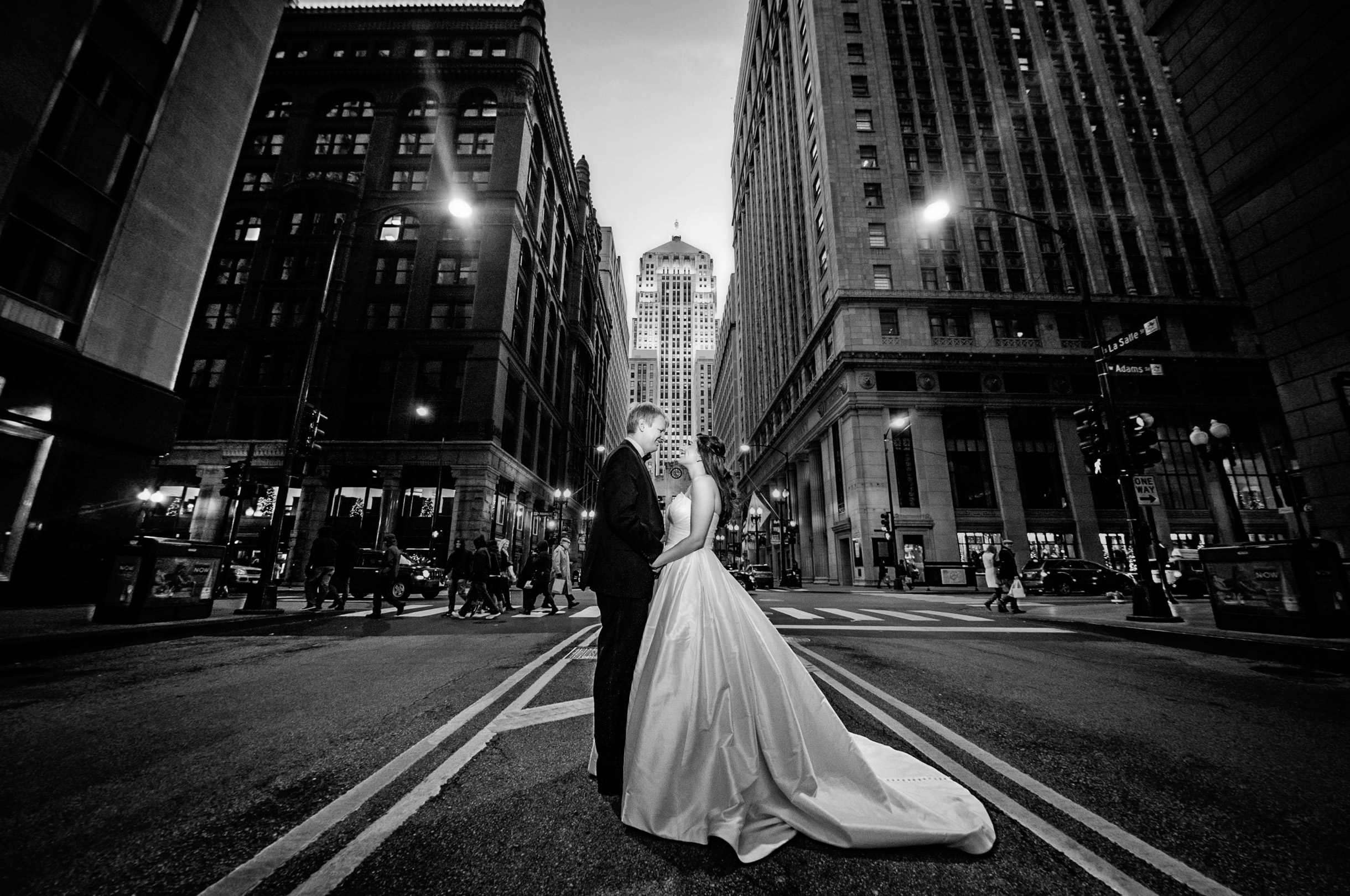 Black and White photo of bride and groom on LaSalle street in Chicago in front of the Board of Trade in traffic-177