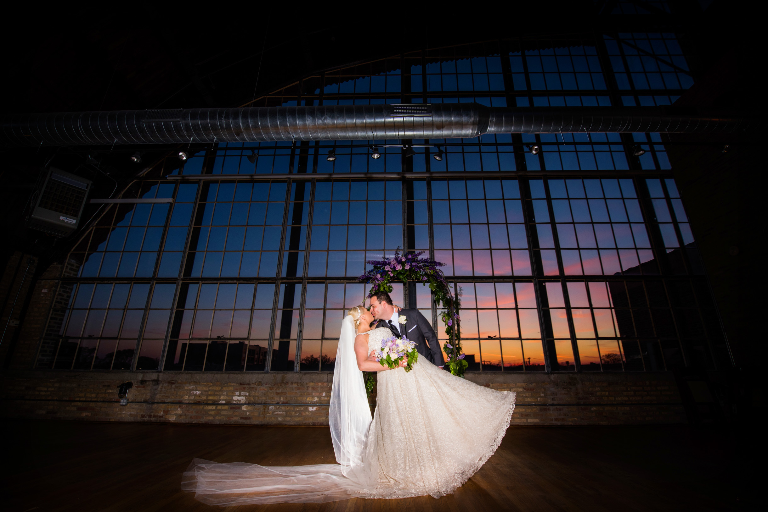 Bride and Groom dipping and kissing at sunset in the Ravenwood Event Center