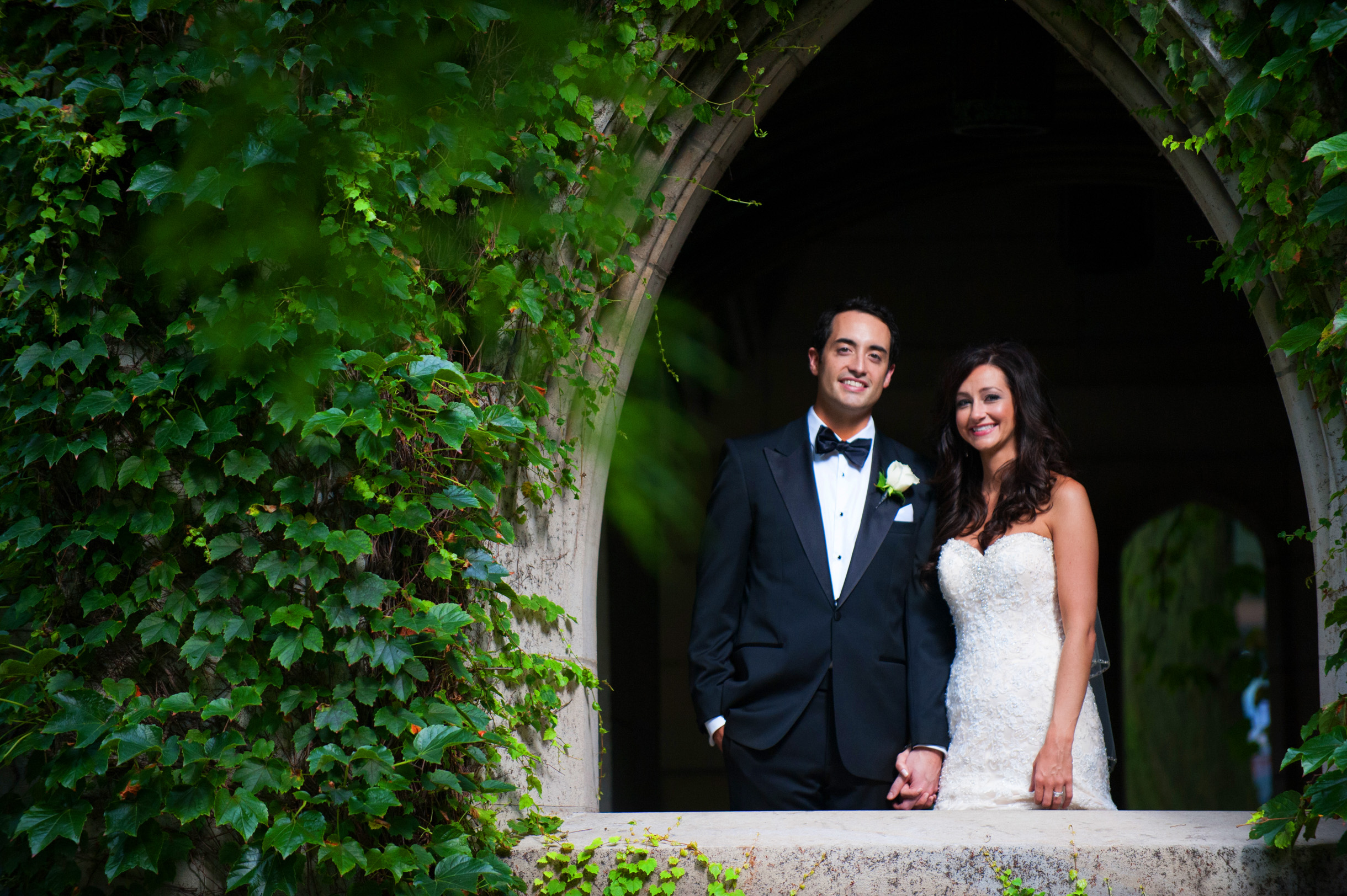 Bride and Groom inside church window with ivy surrounding them