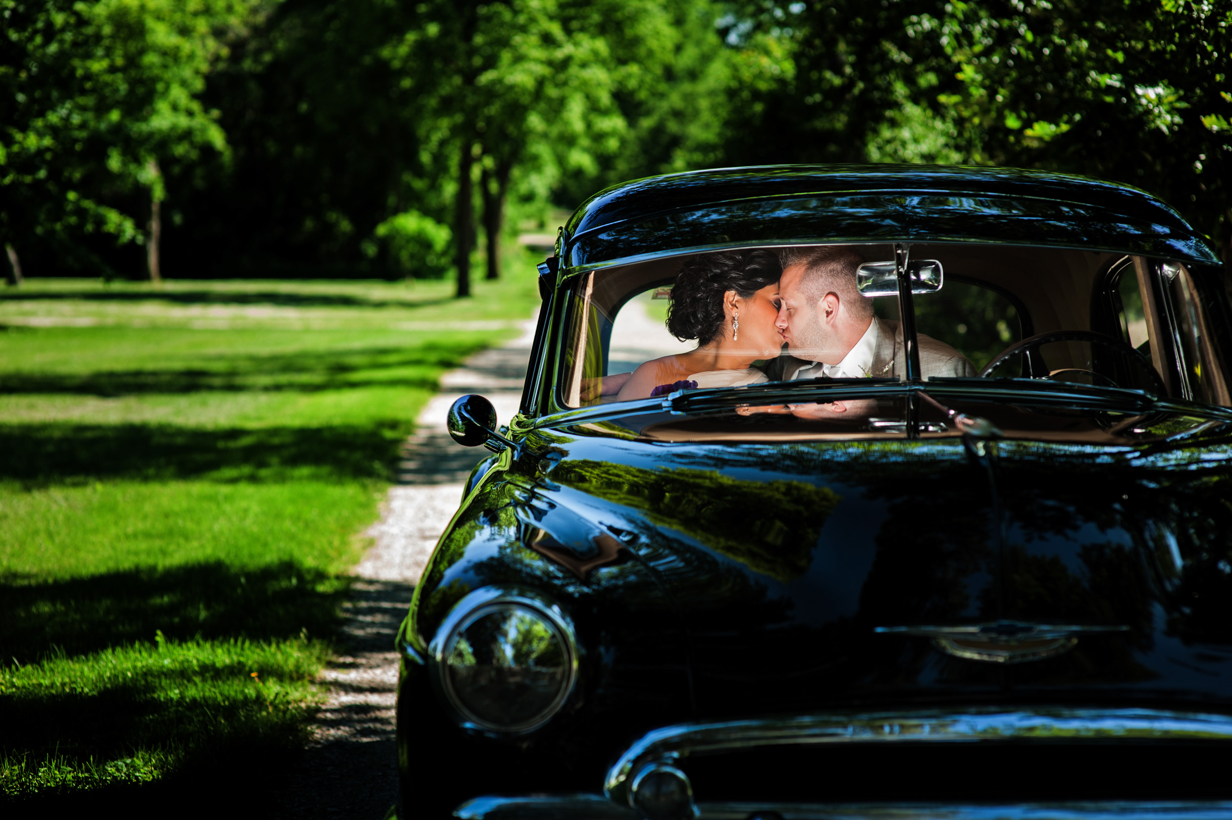 Bride and Groom kissing inside a classic car on a country road