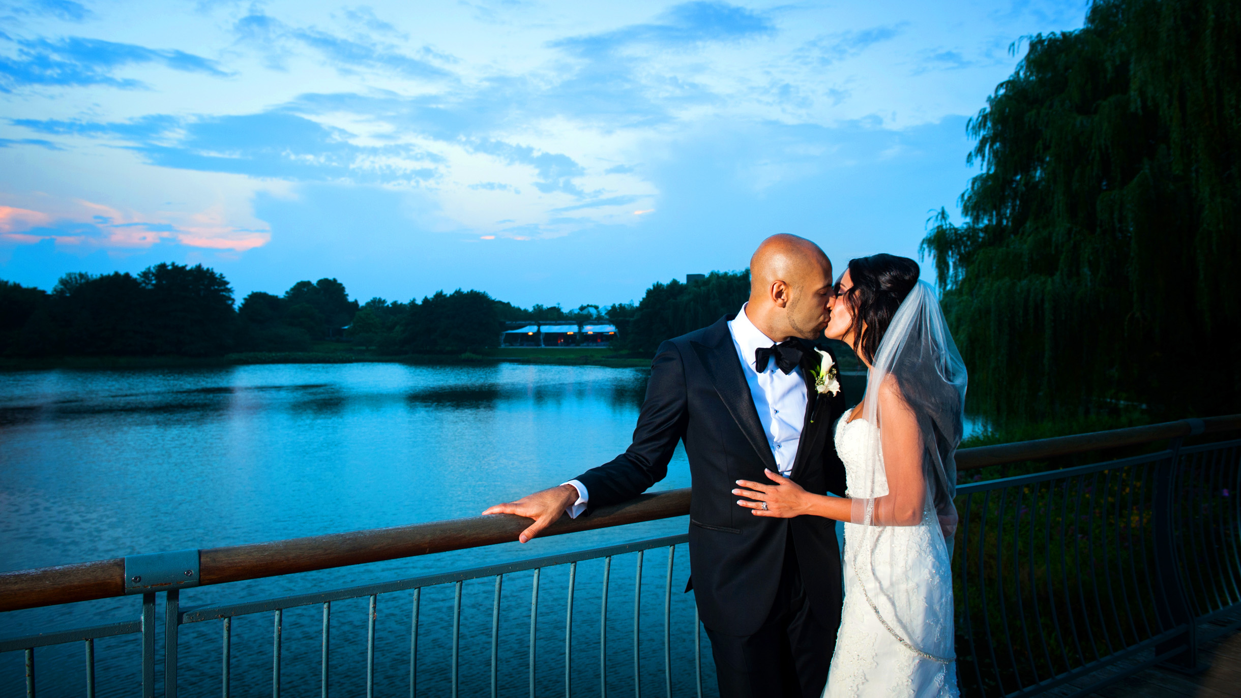 Bride and Groom kissing on bridge in front of the mcginley pavilion at the Chicago Botanic Garden-107