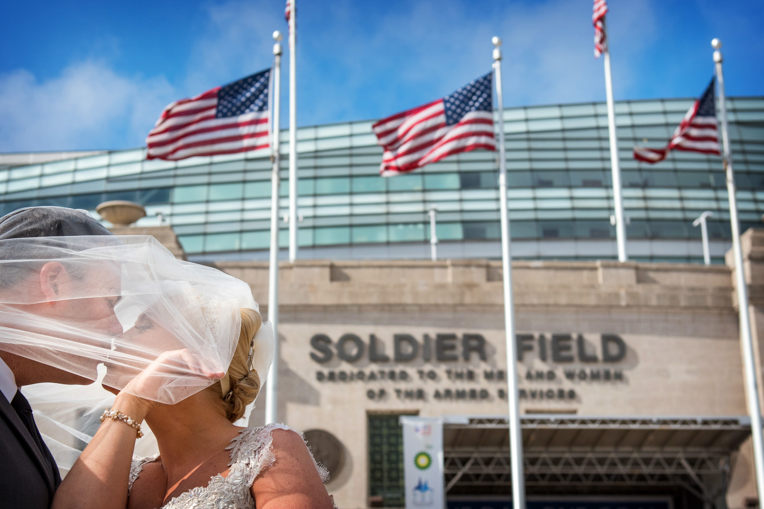 Bride and Groom kissing under veil at Soldier Field in Chicago