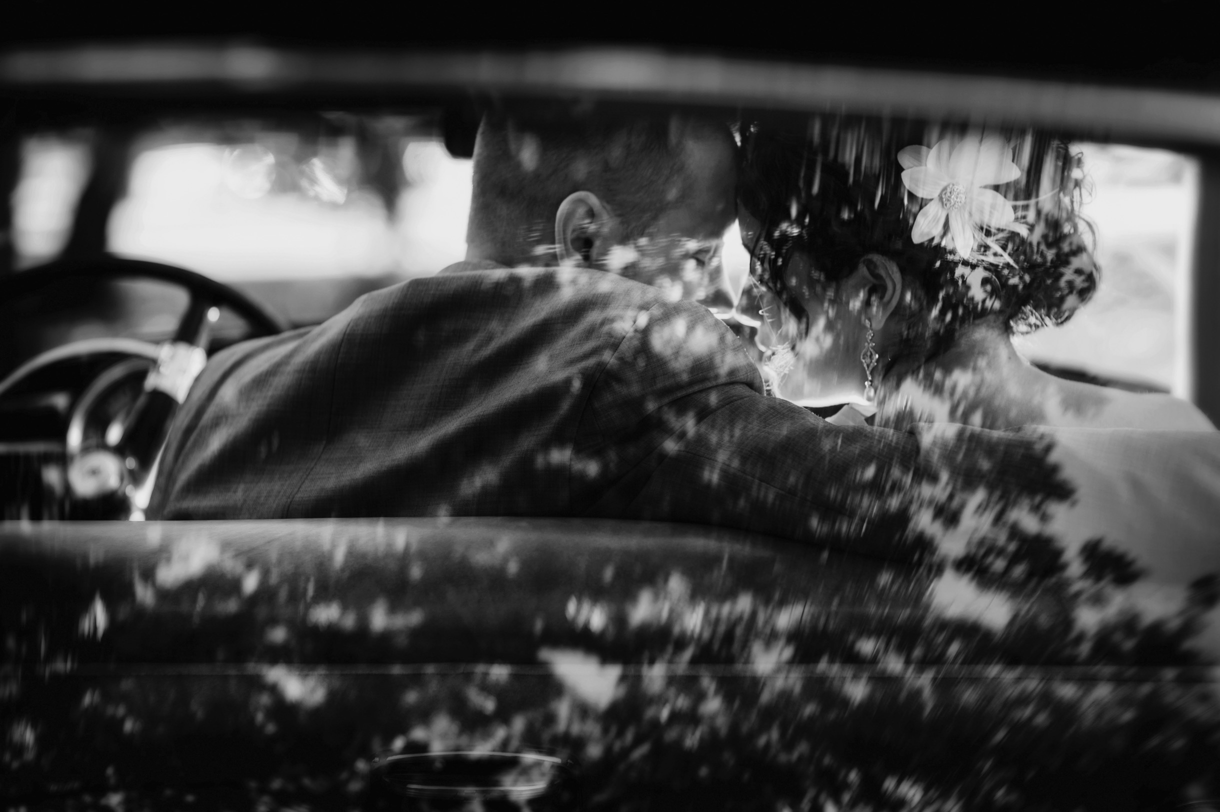 Bride and Groom romantically kissing in a classic car Photograph in Black and White-019