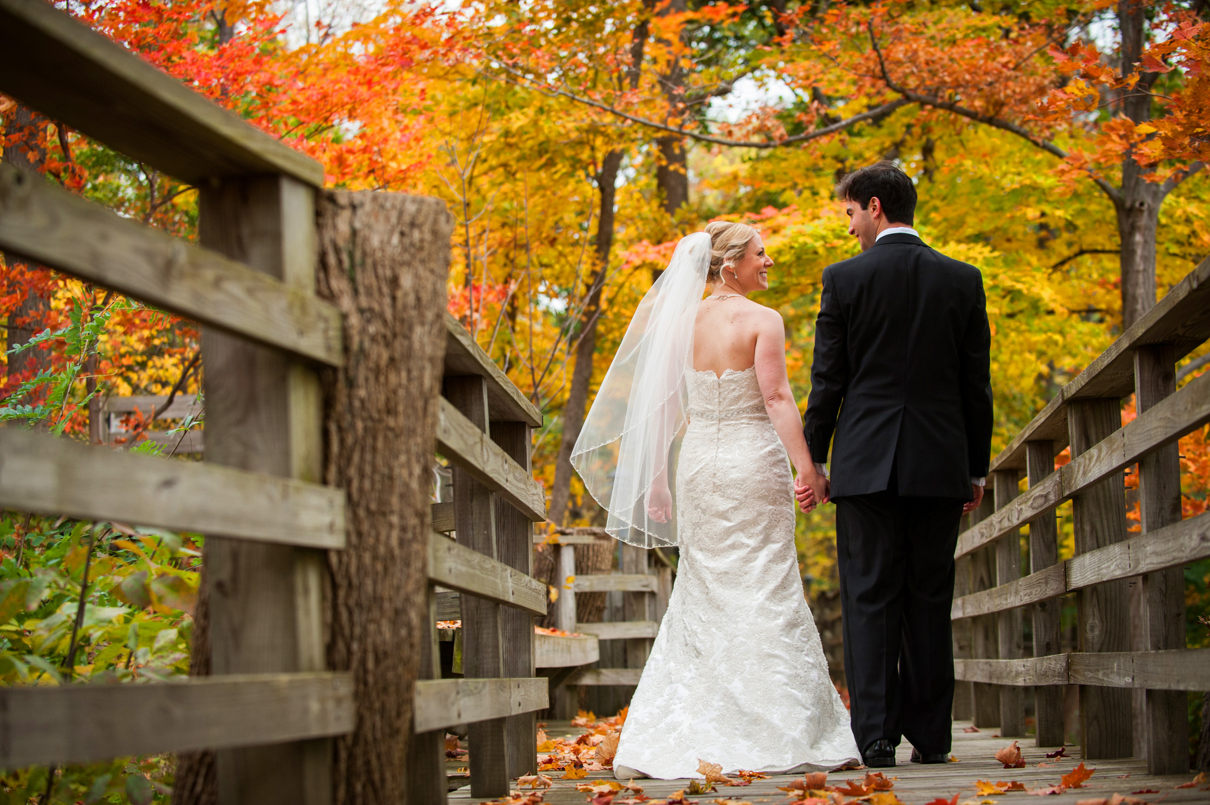 Bride and Groom walking down path hand in hand during their Fall outdoor wedding ceremony-263