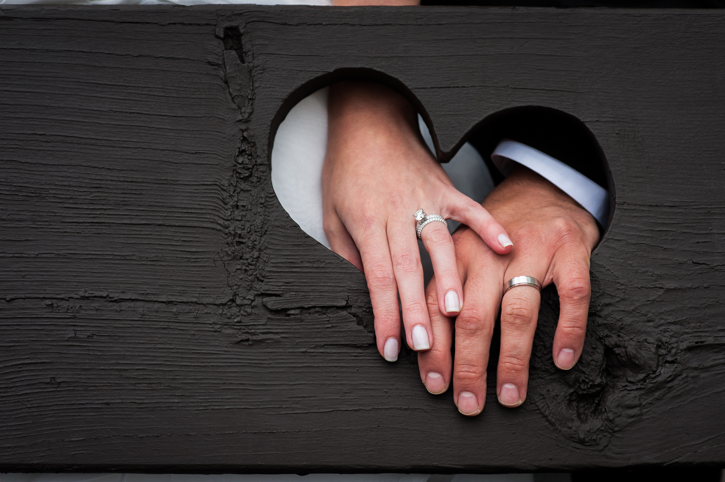Bride and Grooms hands in heart with wedding rings