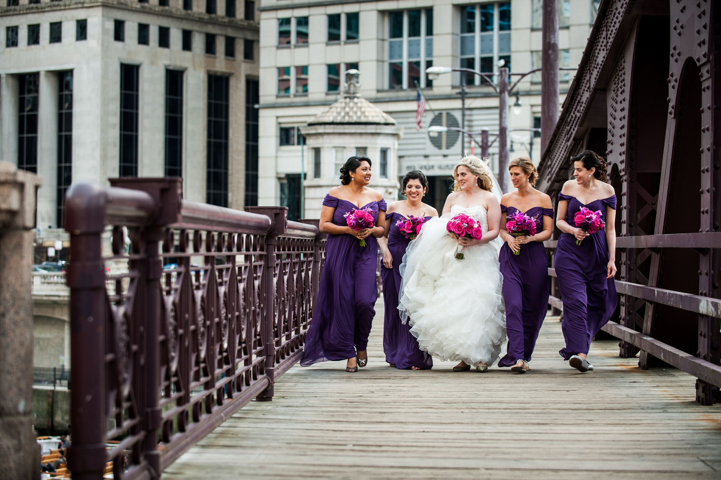 Bride and bridesmaids in purple dresses walking across bridge in downtown Chicago-183