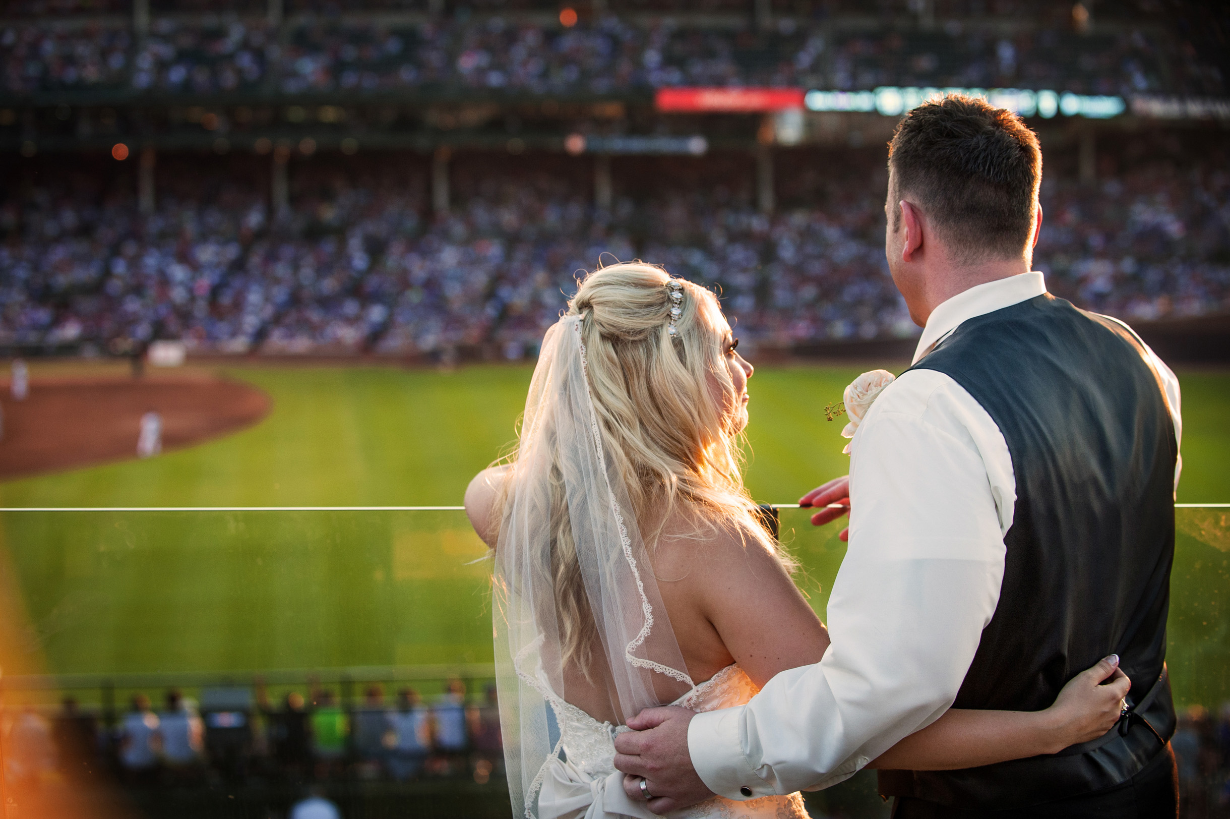 Bride and groom celebrating their wedding day looking into Wrigley Field where the Chicago Cubs play baseball-294