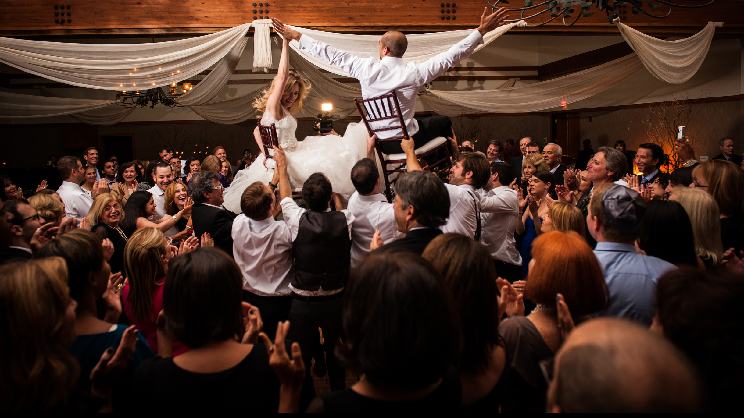 Bride and groom lifted up on chairs above guests during hora a jewish wedding reception tradition-328