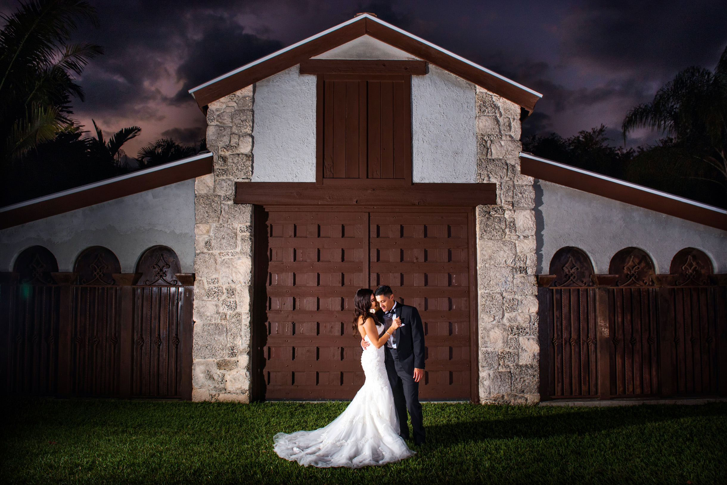 Bride and groom posing at sunset beneath a Spanish style wedding reception venue at the Cooper Estate in South Florida-035