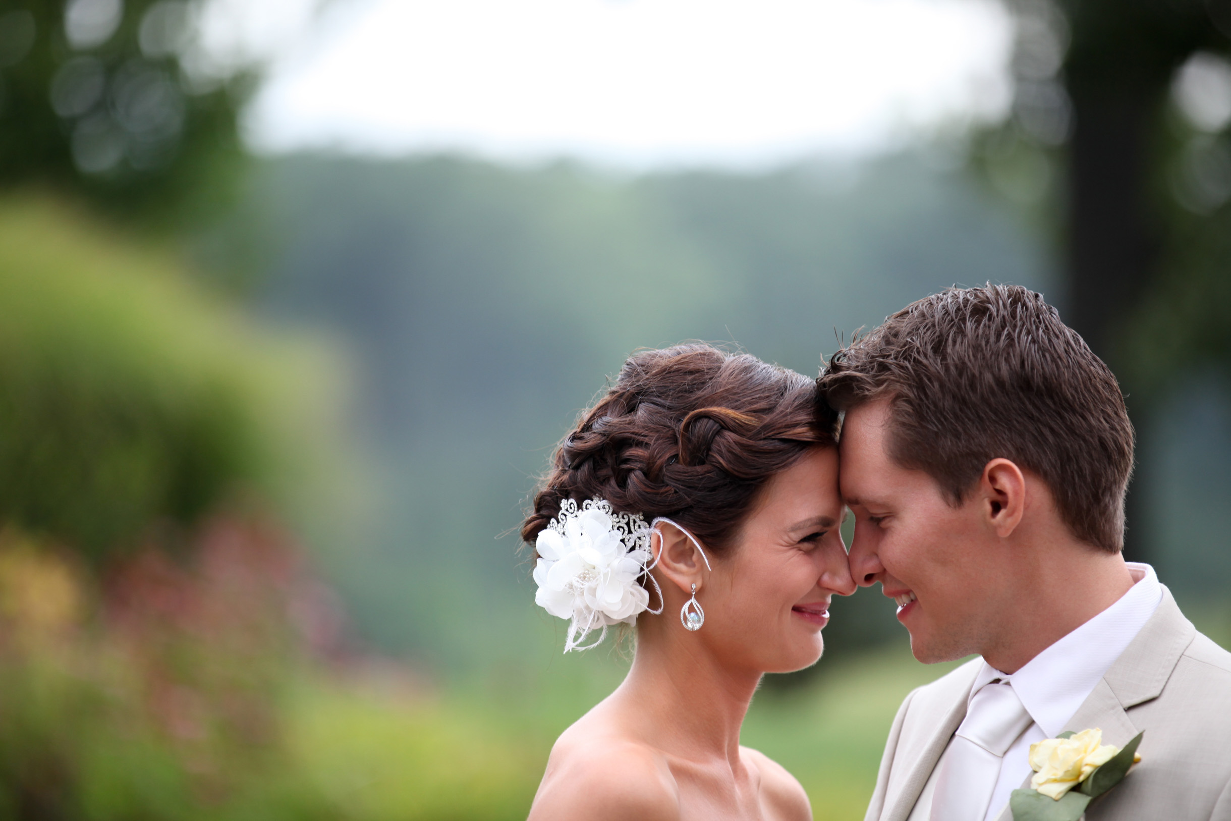 Bride and groom resting foreheads together and smiling