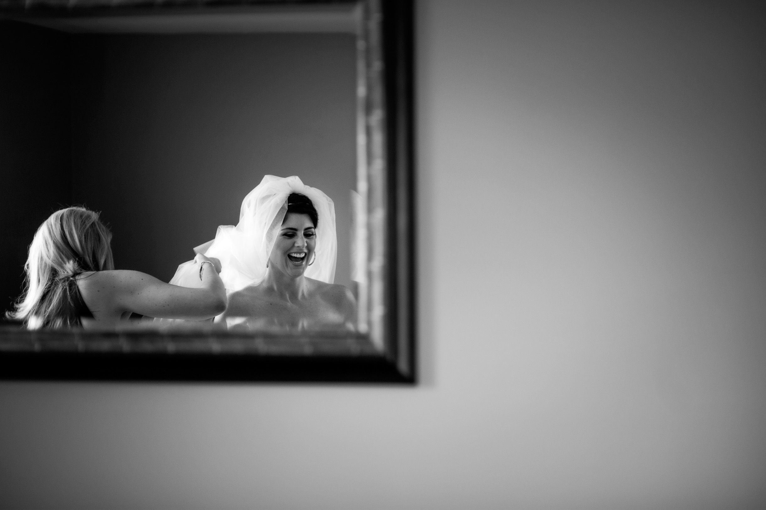 Bride getting her veil put on by her bridesmaid and laughing in the mirror