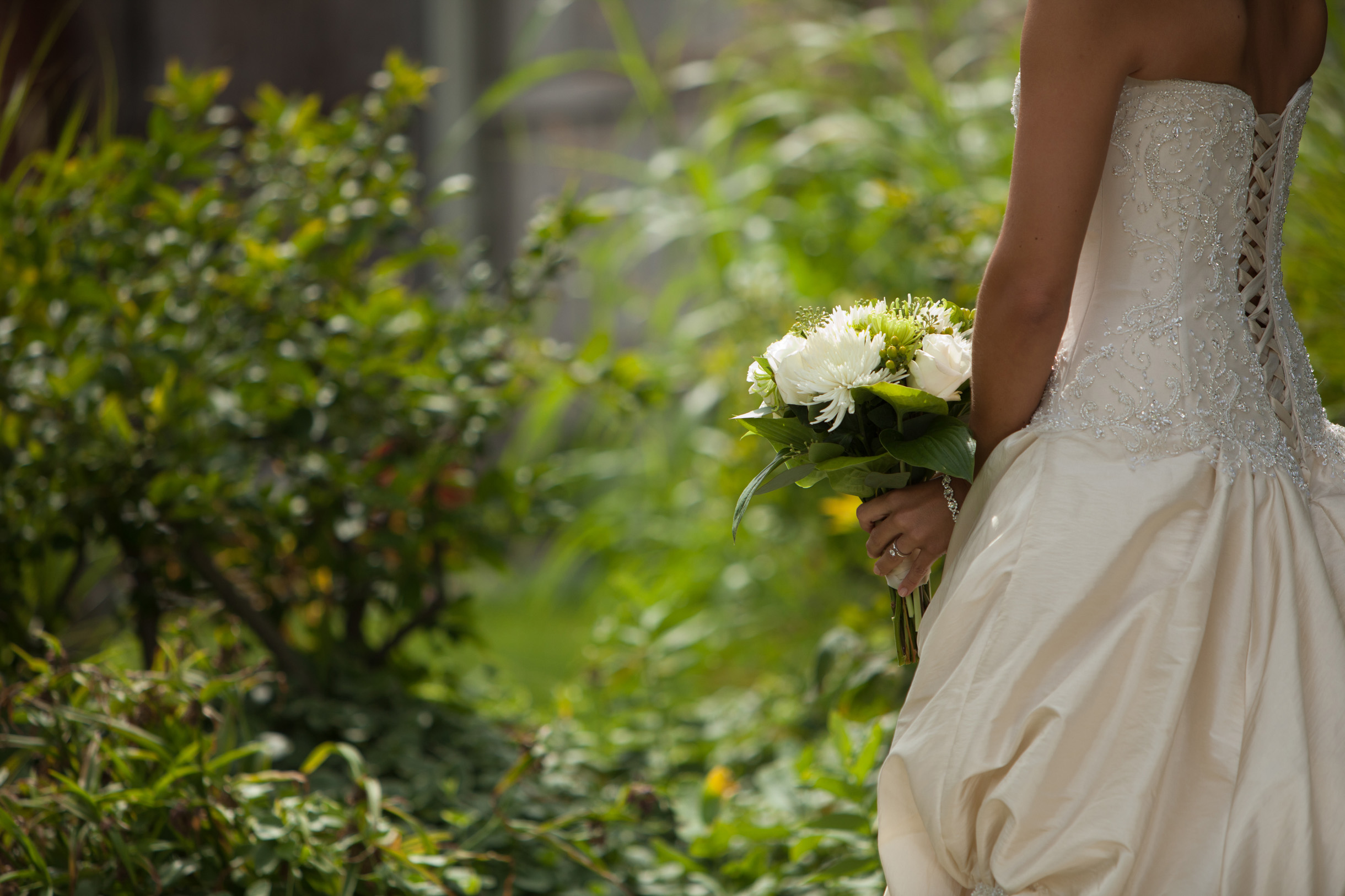 Bride holding bouquet in white dress with tie up back
