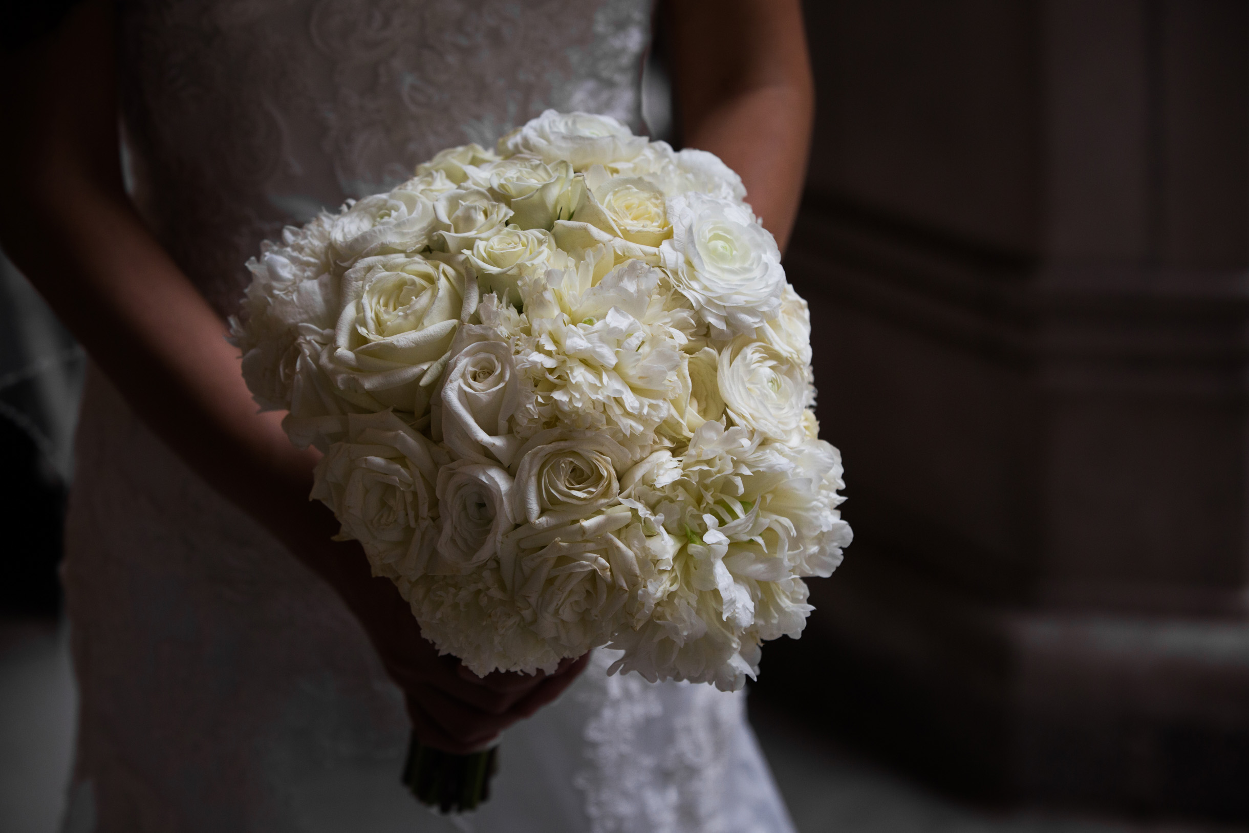 Bride holding white wedding bouquet of flowers and roses on her wedding day