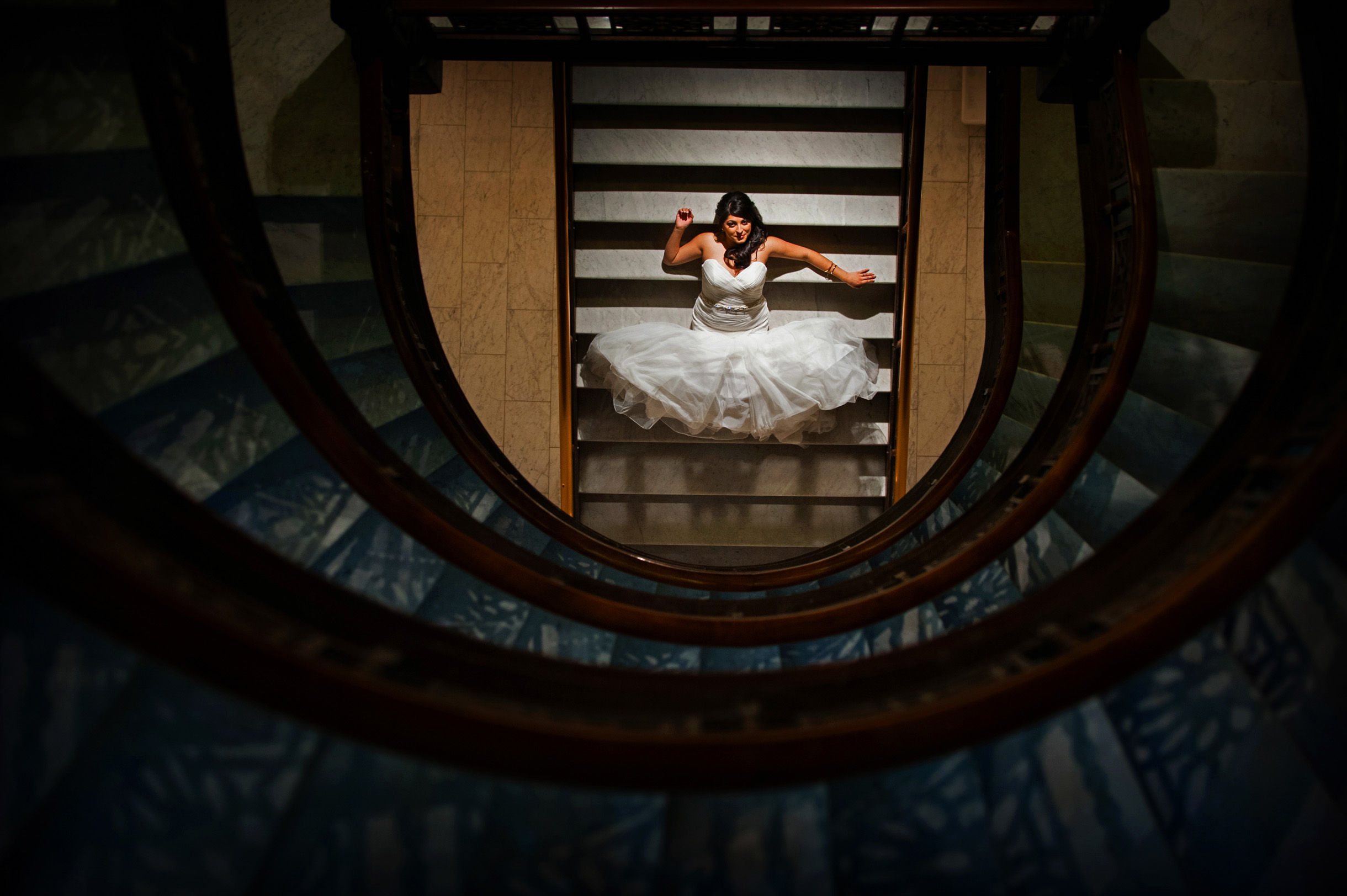 Bride laying down on oriel staircase at the rookery in chicago