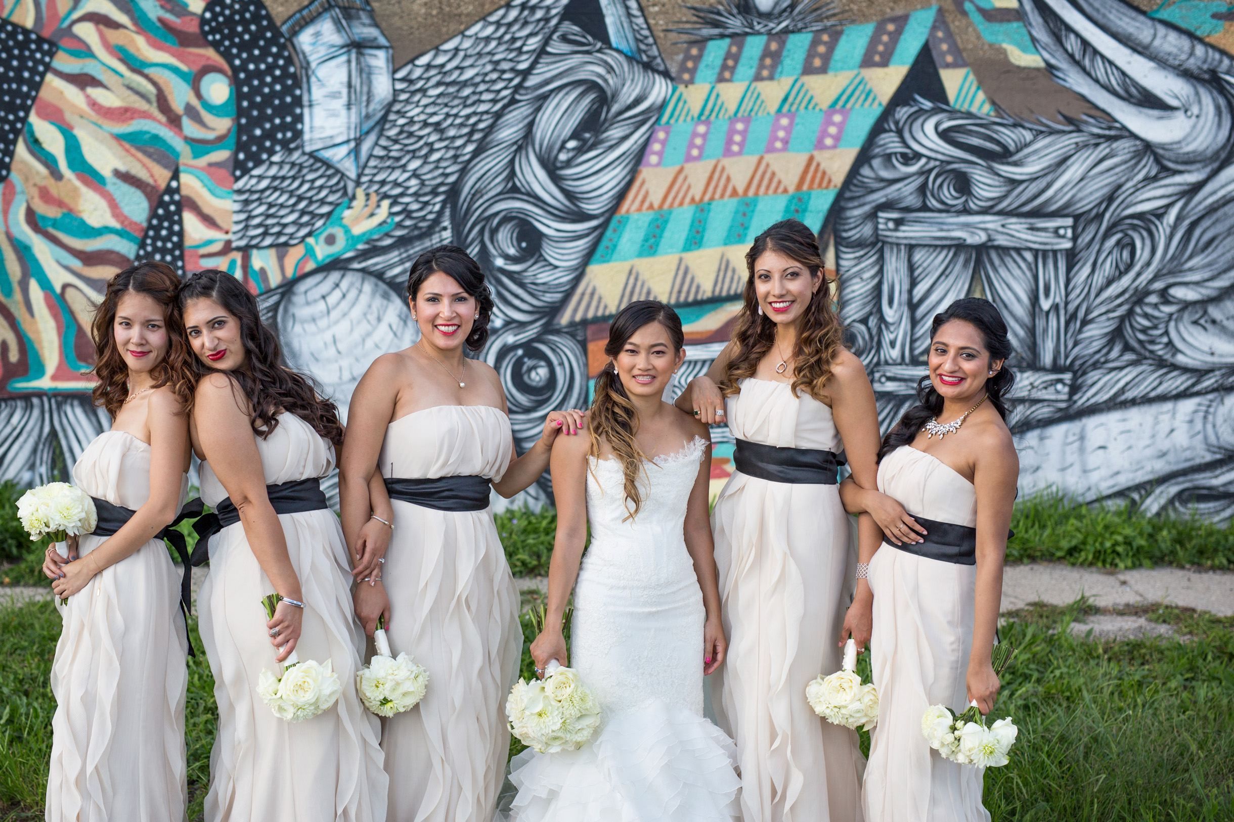 Bridemaids posing with bride in front of graffiti street art mural in Pilsen