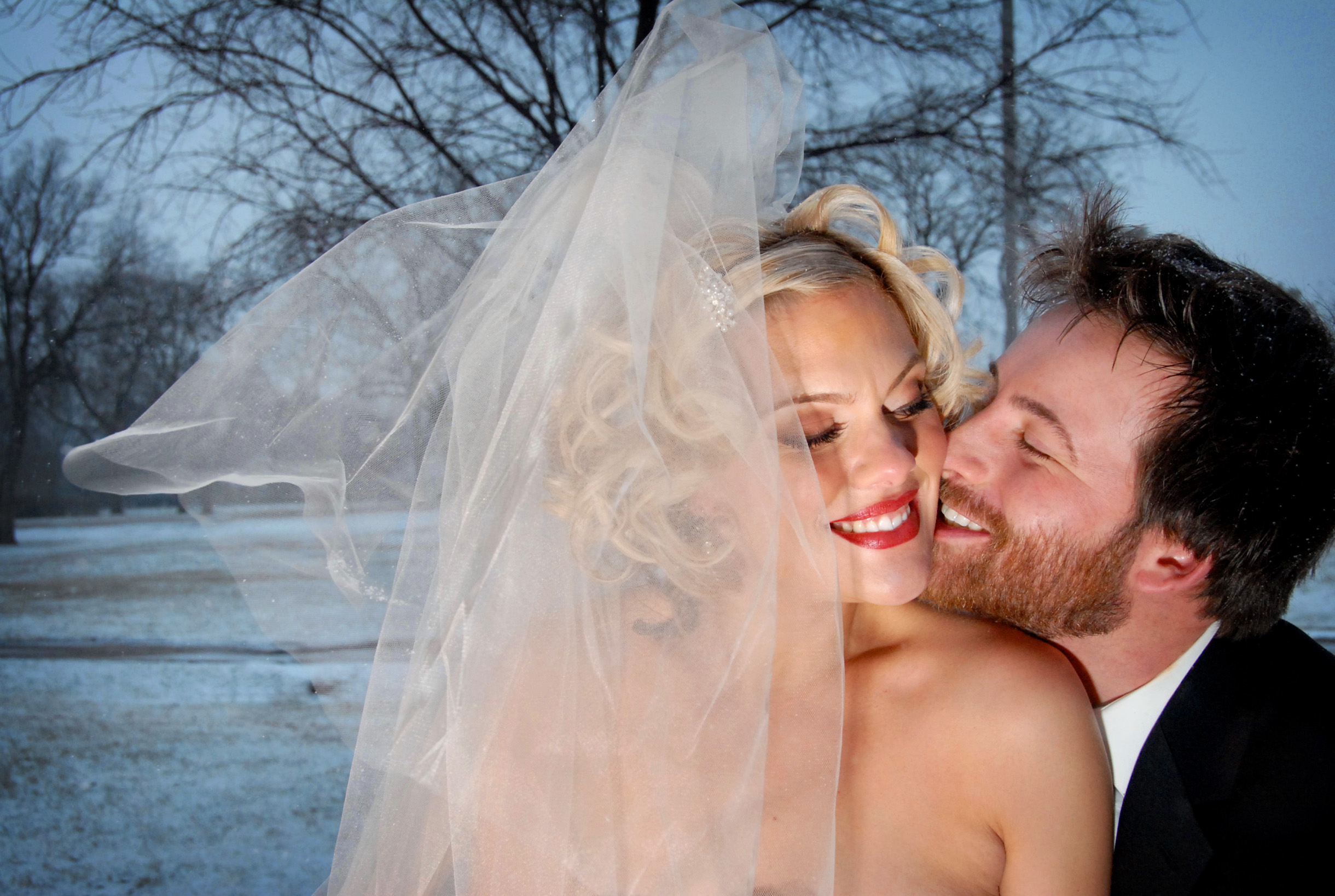 Bride's veil blowing in the winter with snow on the ground and groom cuddling with bride-086