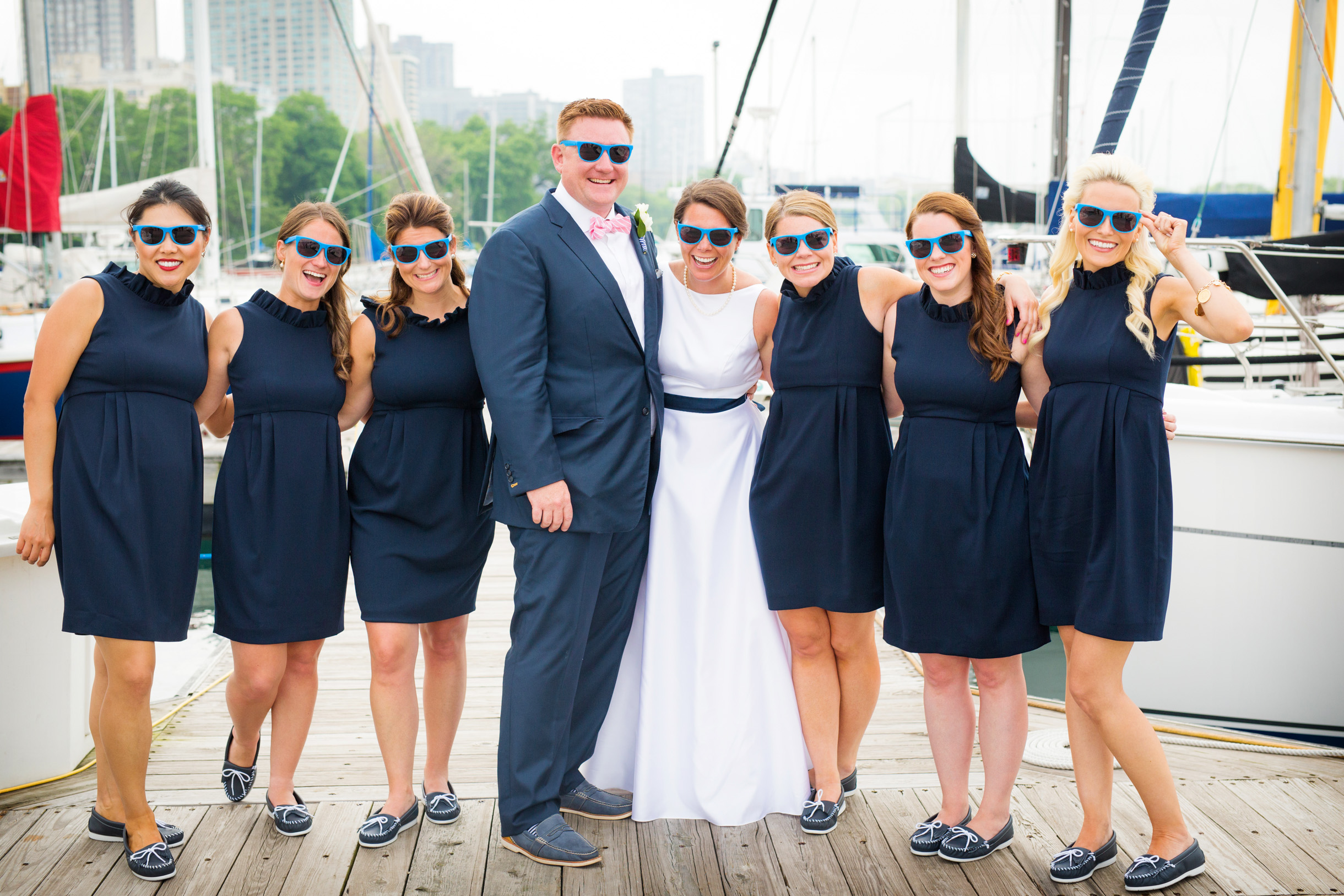 Bridesmaid wearing wedding sunglasses with bride and groom in front of their boat at the Chicago Yacht Club-350