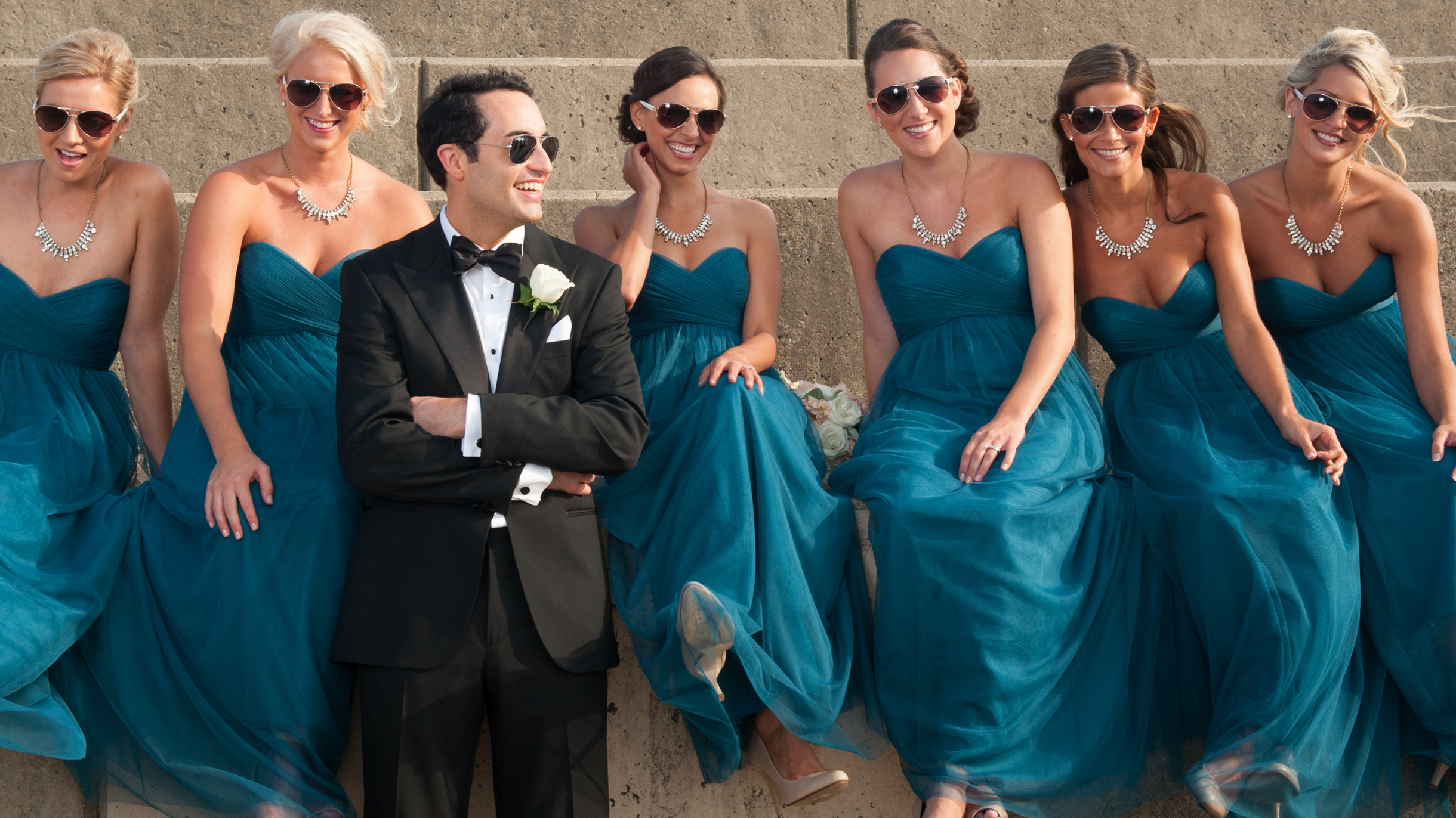 Bridesmaids posing with groom in sunglasses