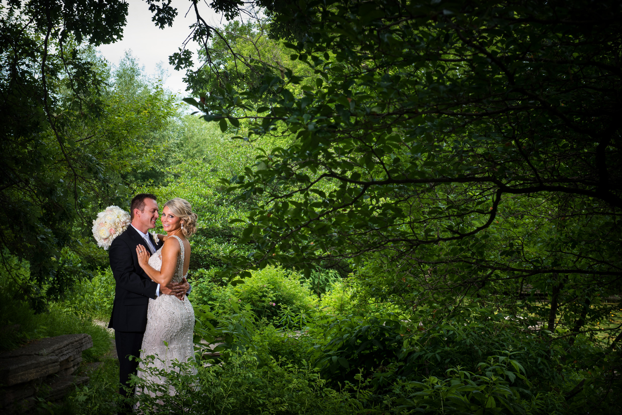 Dramatic Bride and Groom photo in nature surrounded by trees and lush vegetation-039