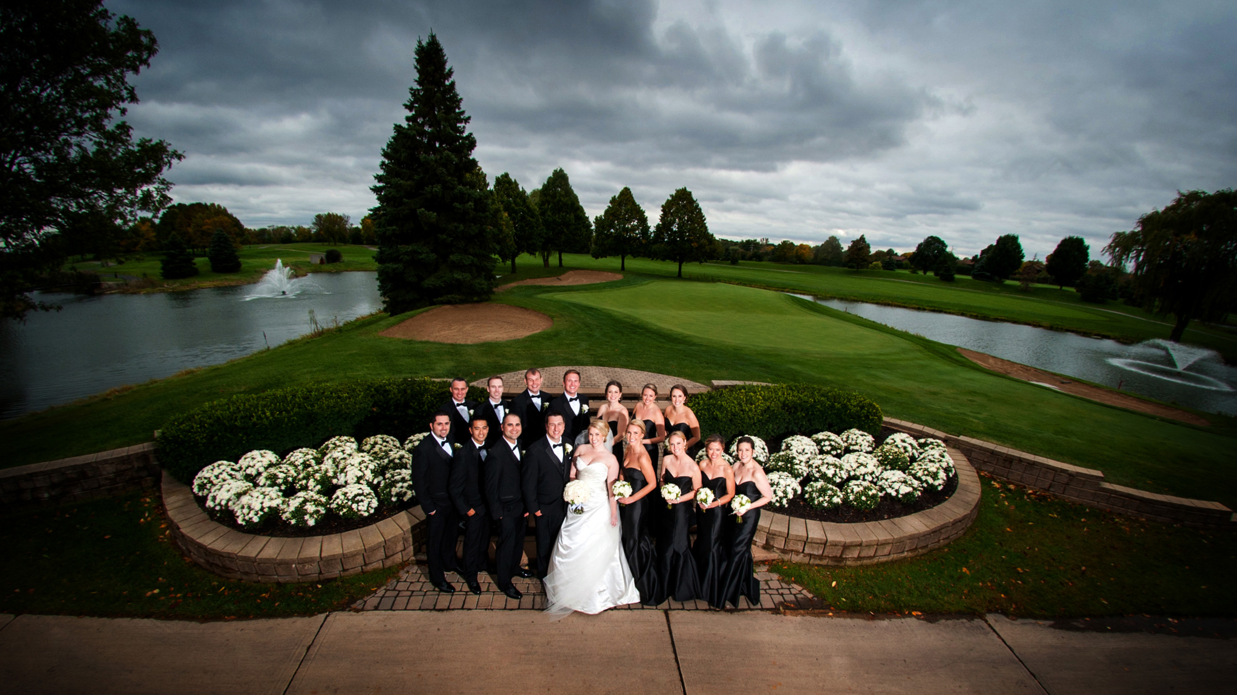 Dramatic bridal party photo on golf course before the rain storm