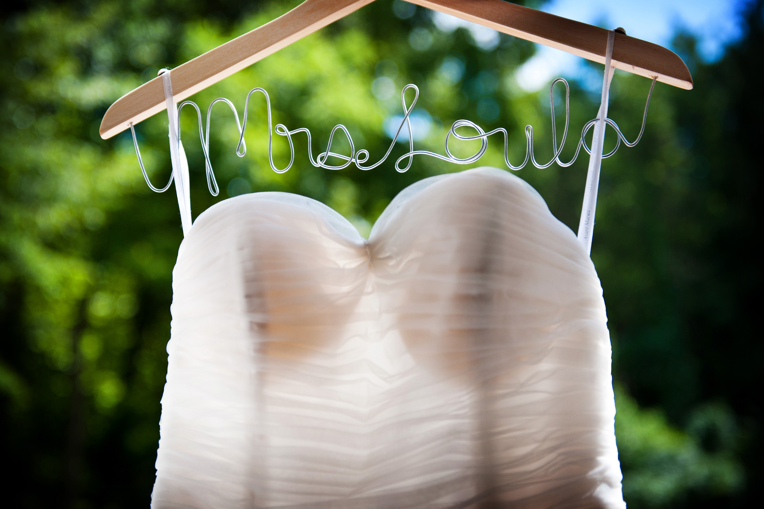 Dress hanging from custom DIY hanger made from bent metal to spell her married name
