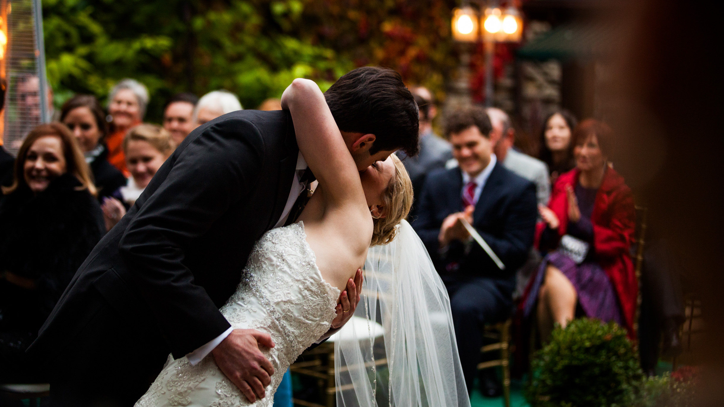 Groom dipping bride in dramatic kiss after their outdoor wedding ceremony