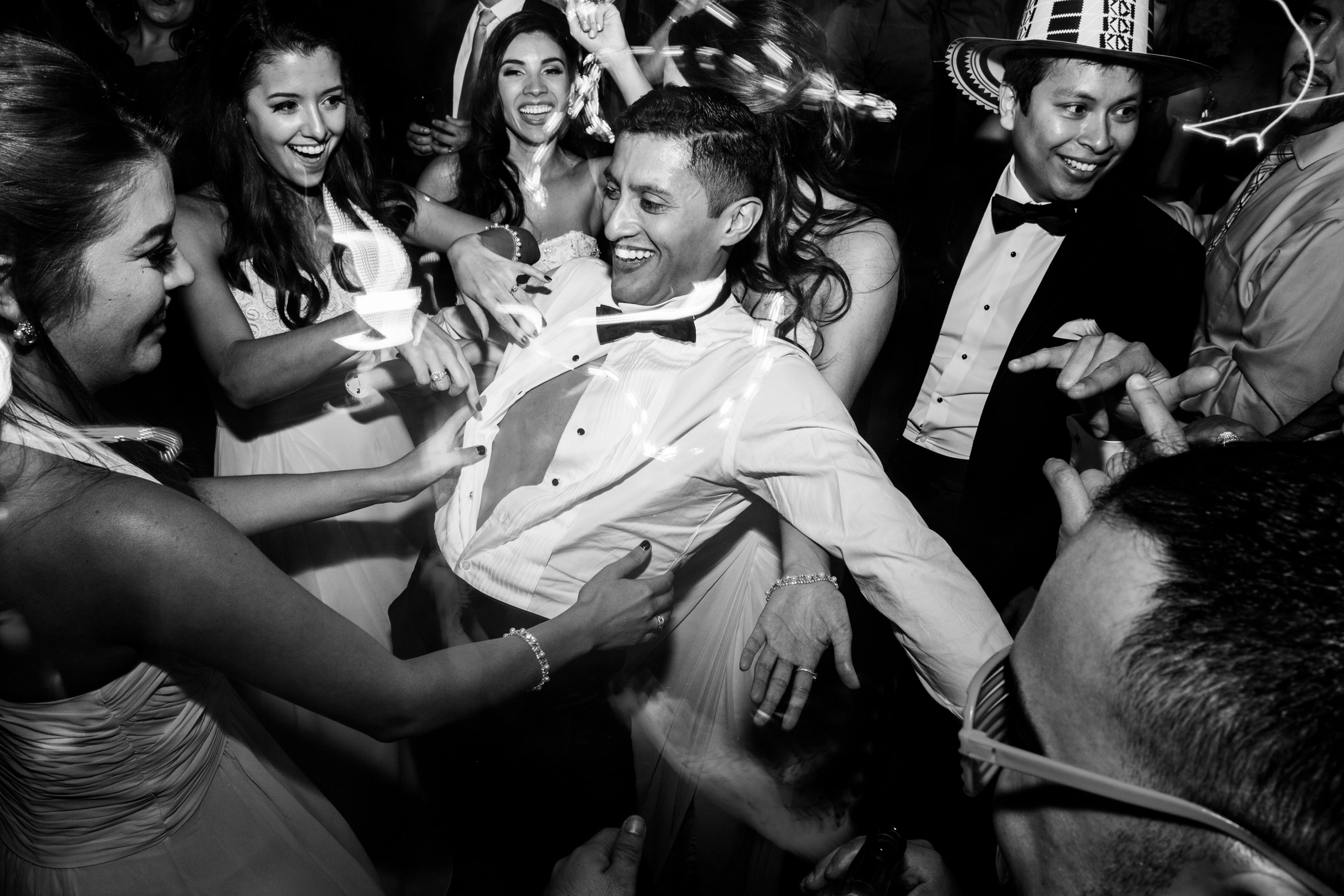 Groom having his shirt ripped off by bridesmaids at wedding reception on the dancefloor-347