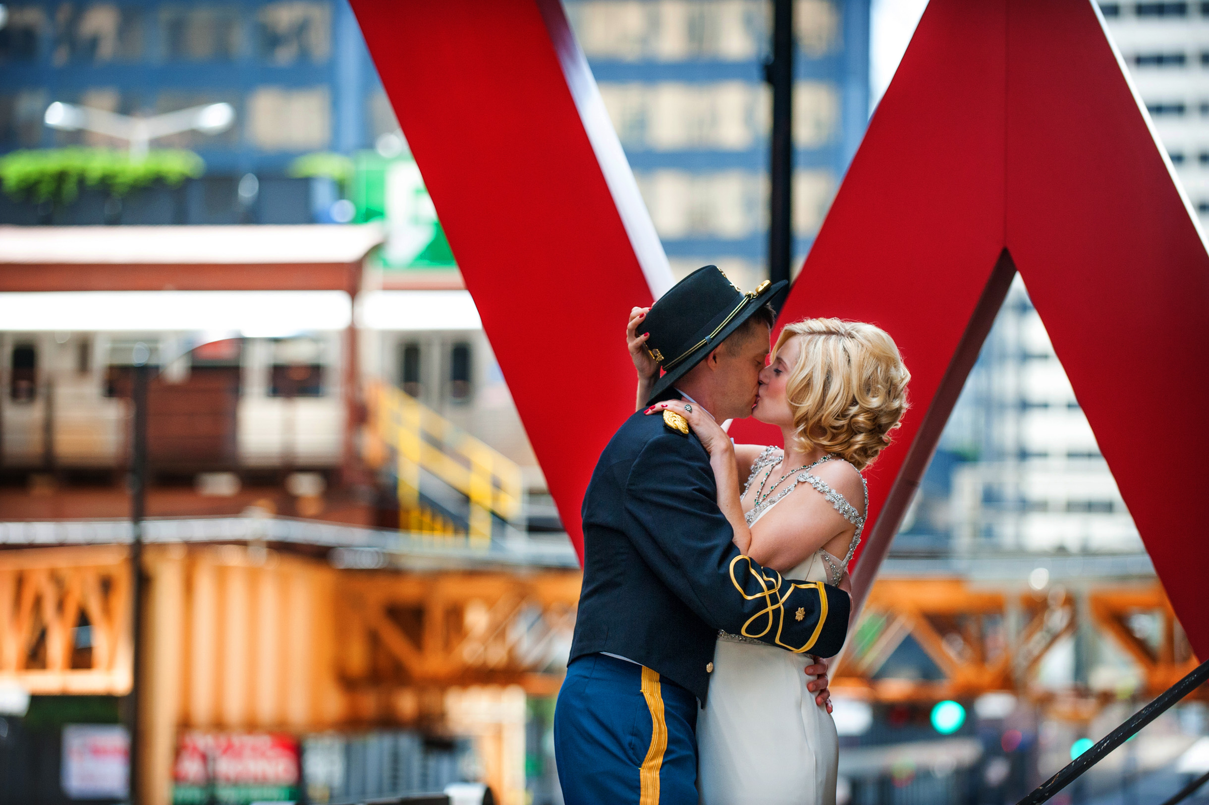 Military groom kissing bride on top of the marquee of the W Hotel in downtown Chicago as the El train passes in the background-348