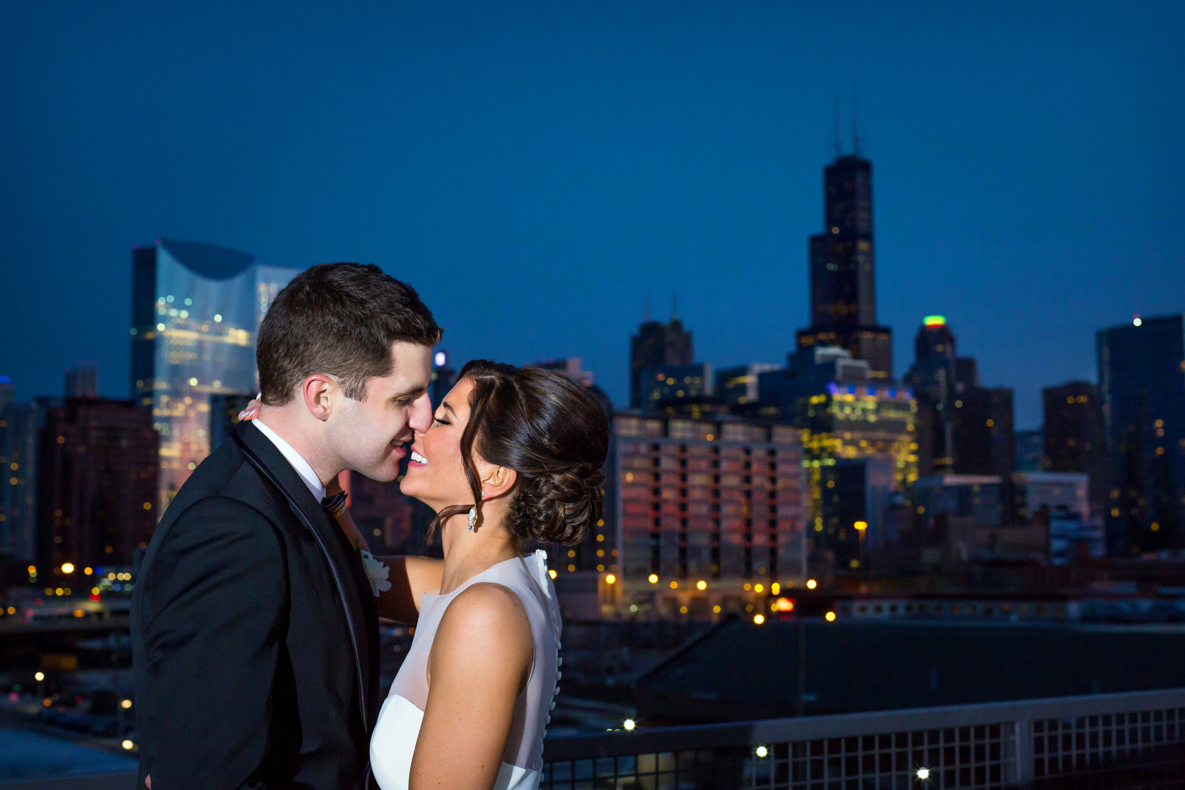 Rooftop photo of Bride and Groom kissing at sunset with Chicago buildings in the background-250