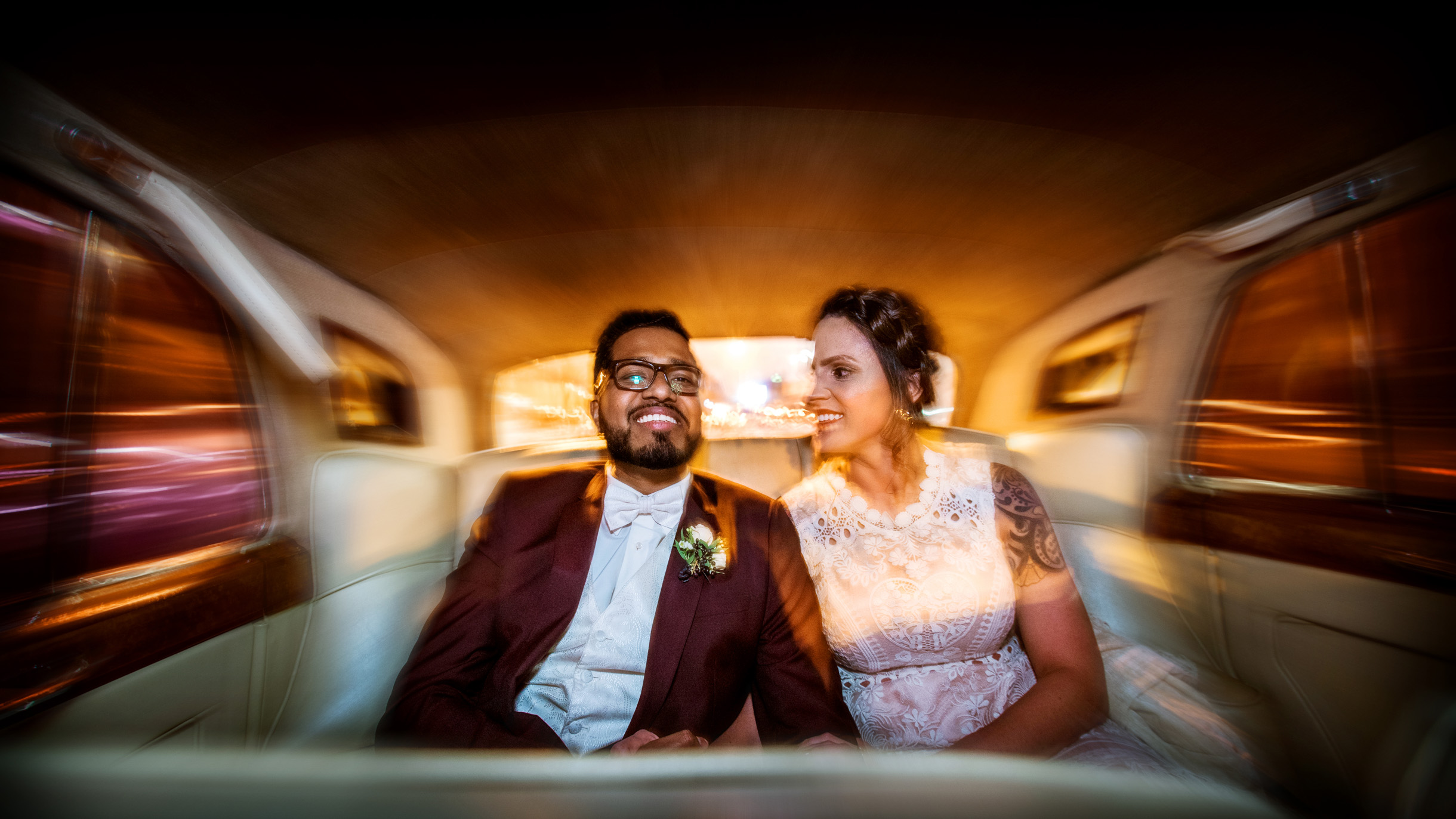 Saturated colorful light streak photo of bride and groom in the back of a classic car-282