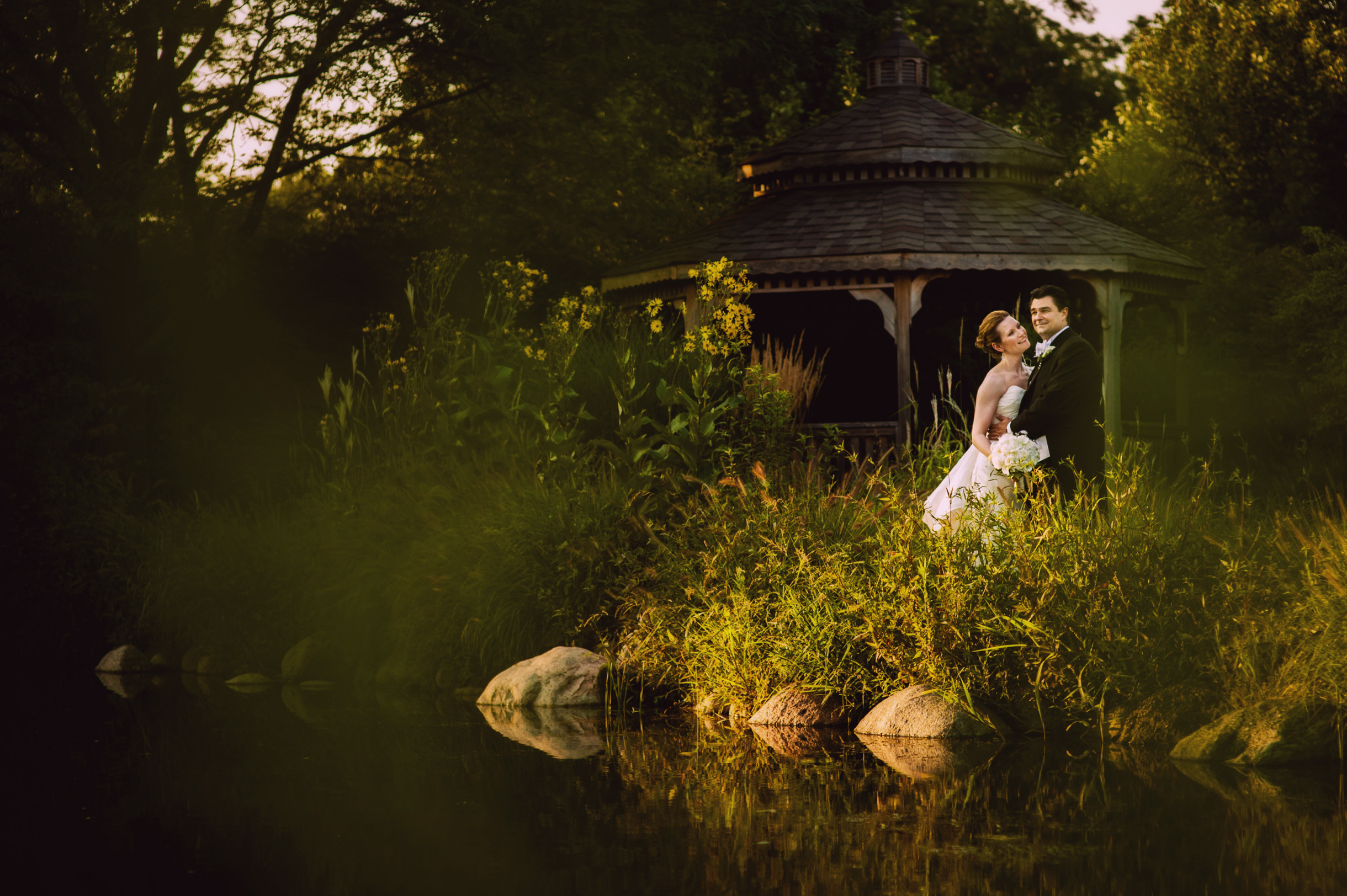 Sunset wedding photo of bride and groom by a gazebo and a lake