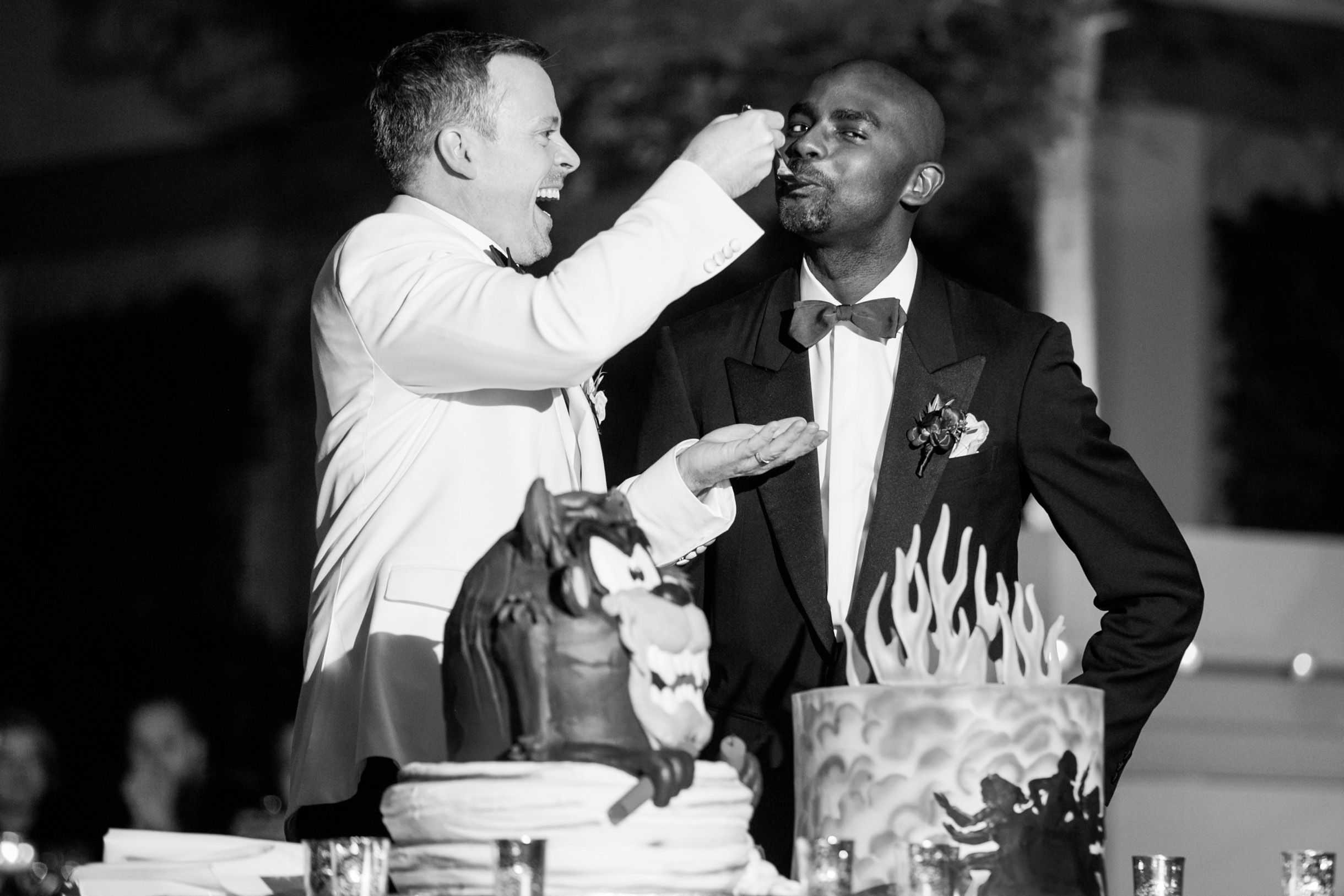Two same sex grooms feeding each other wedding cake