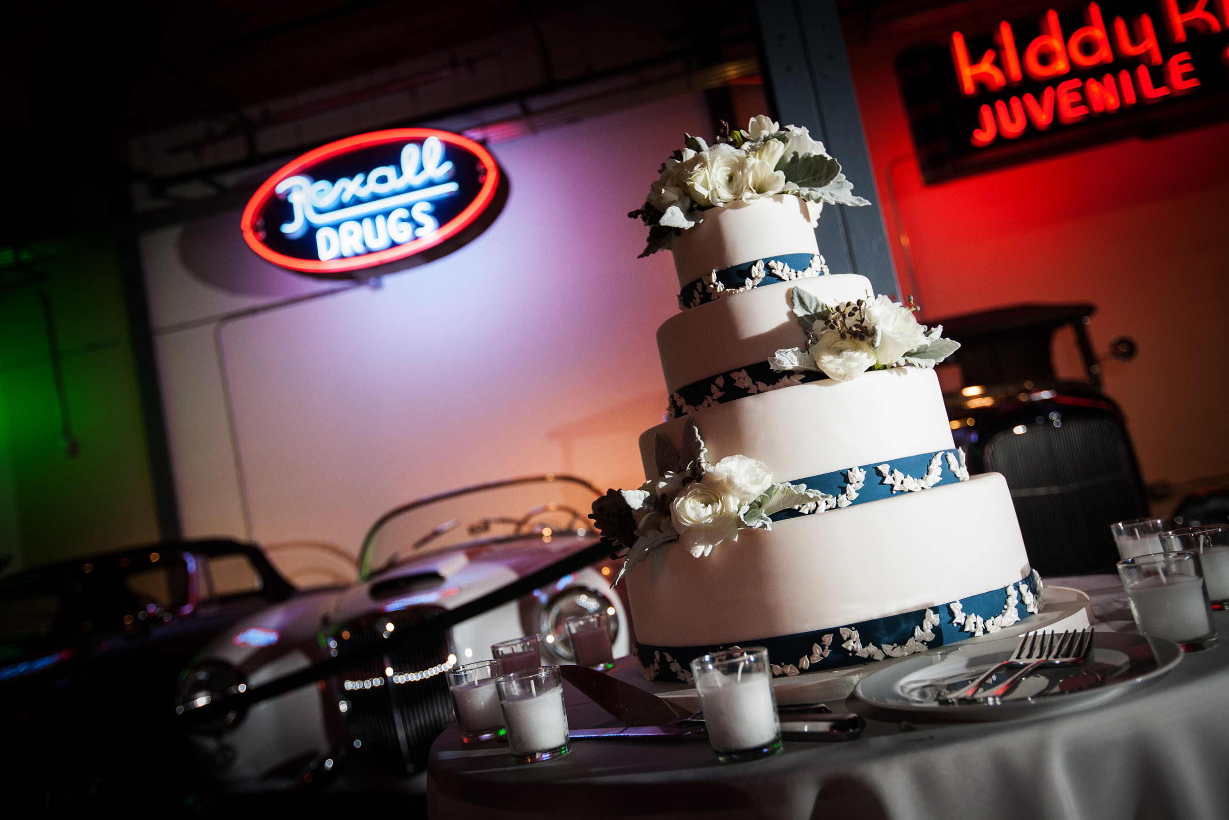 Wedding Cake in front of classic cars at Ravenswood Event Center