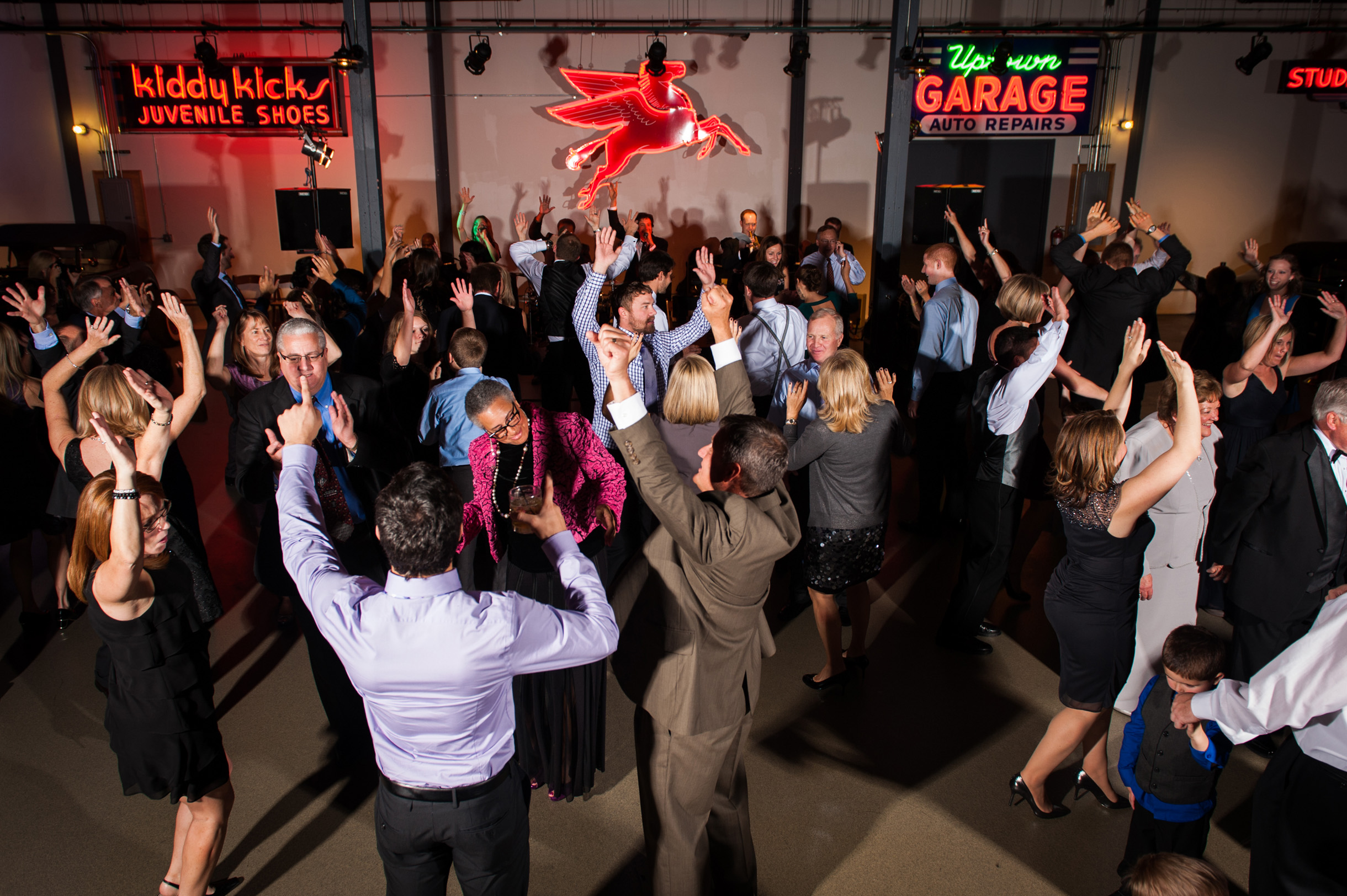 Wedding band performing at the Ravenswood Event Center while guests dance in front of neon signs and classic cars at industrial wedding venue-134