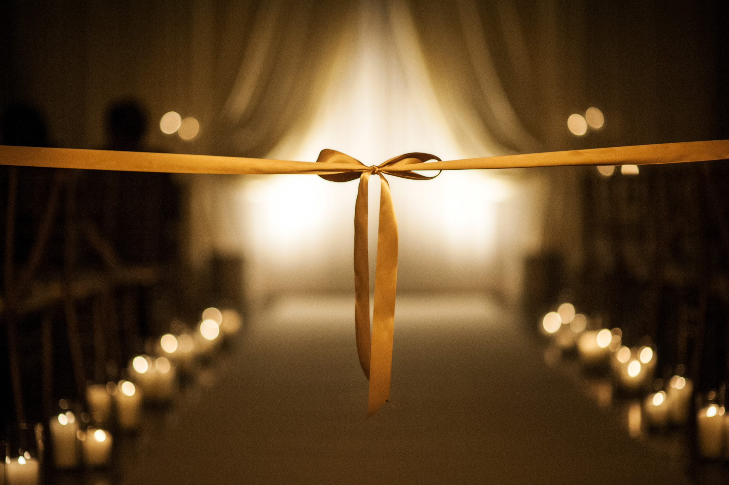 Wedding bow on aisle at candlelit ceremony in Chicago