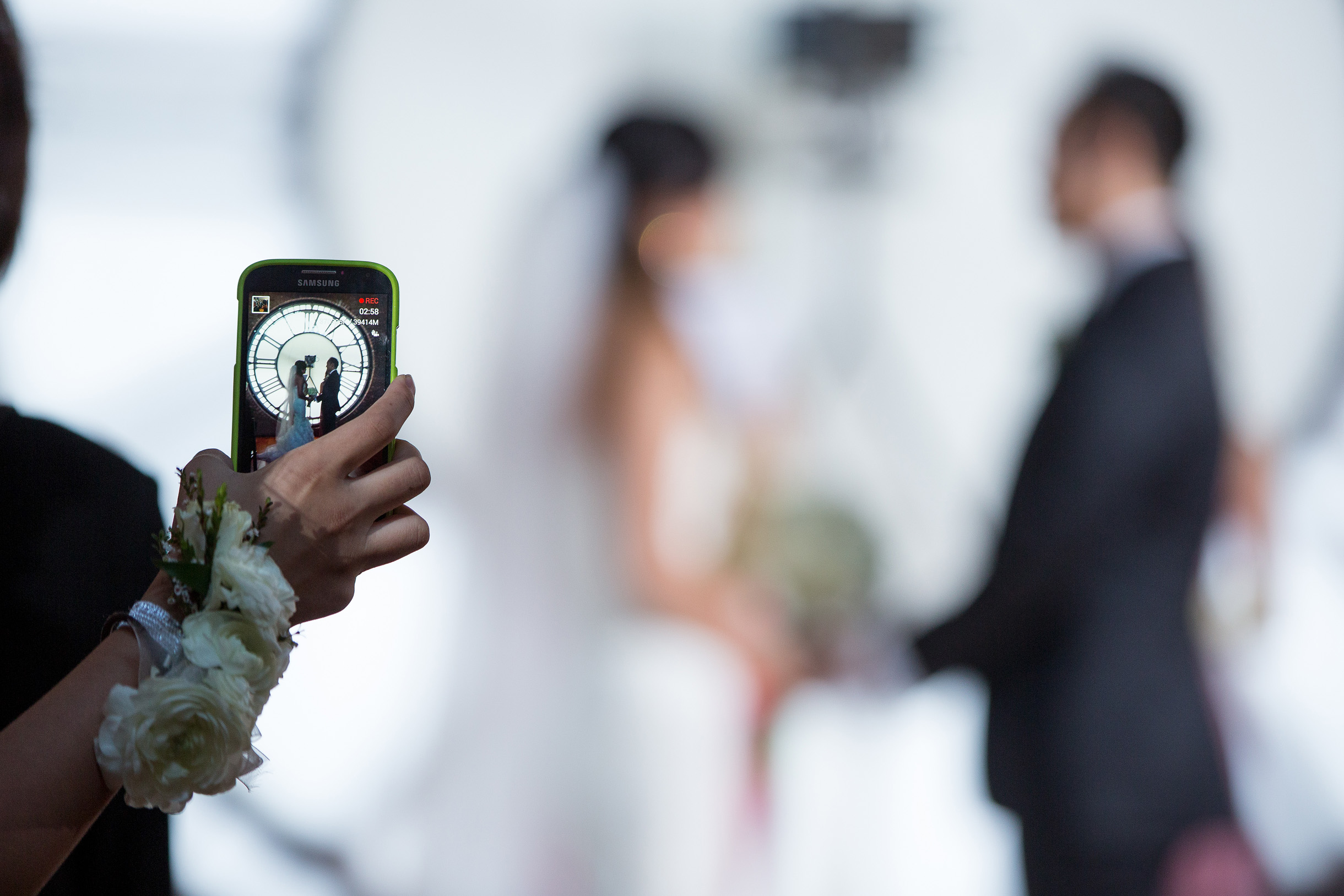 Wedding guest blocking bride and groom with their cellphone during ceremony