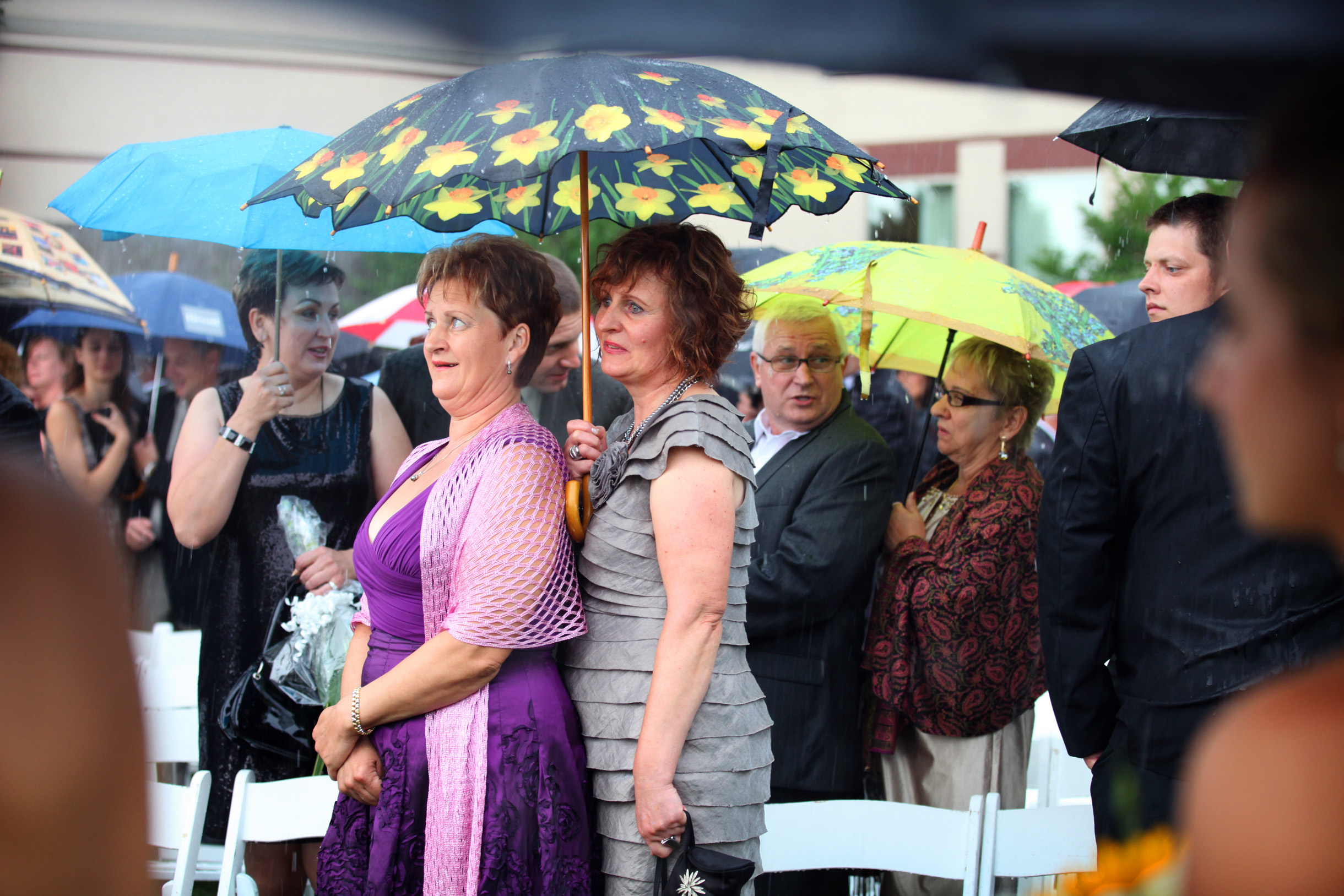 Wedding guests standing under umbrellas during a heavy rain storm downpour