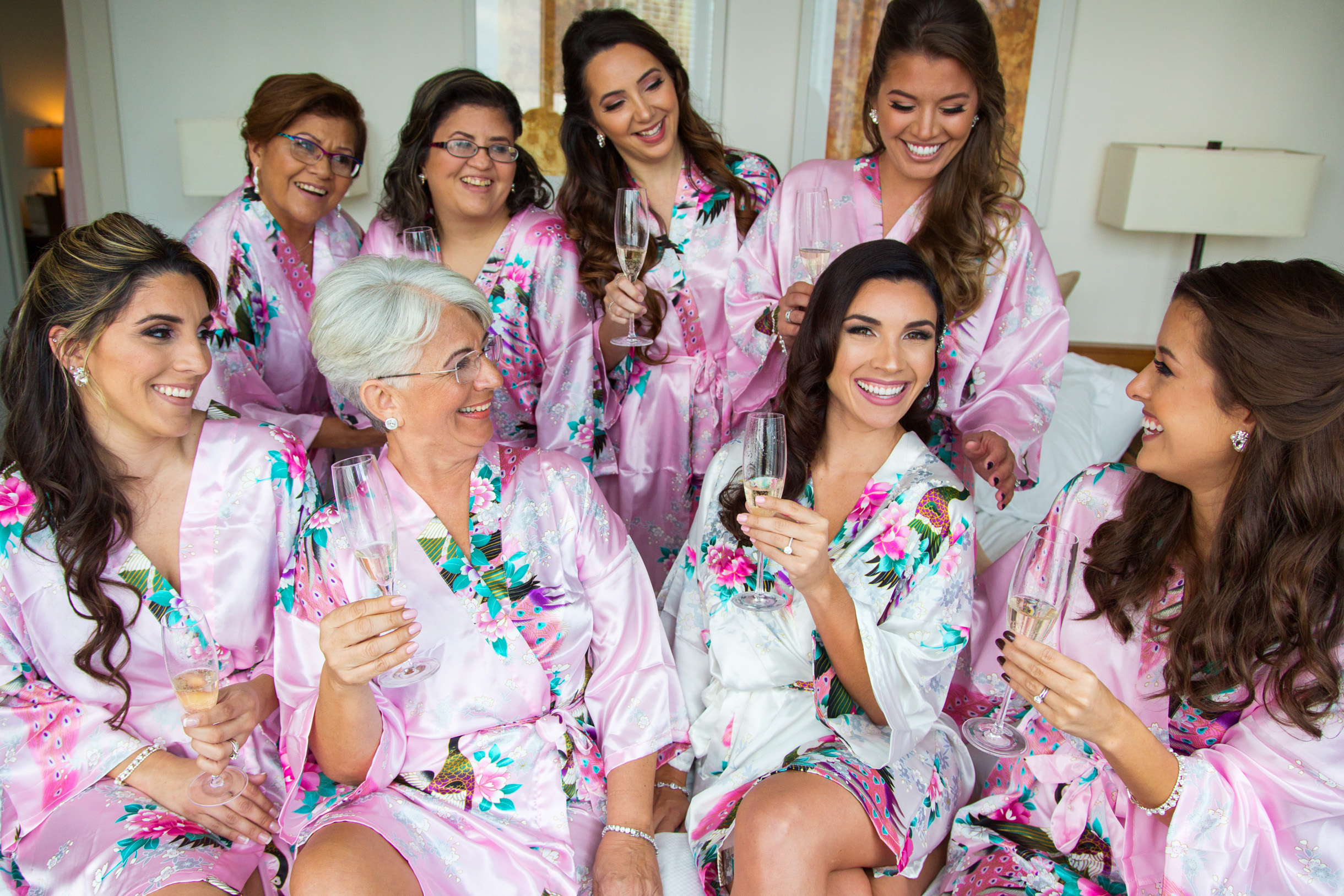 Wedding inspiration photo of bride and bridesmaids posing in their pink robes