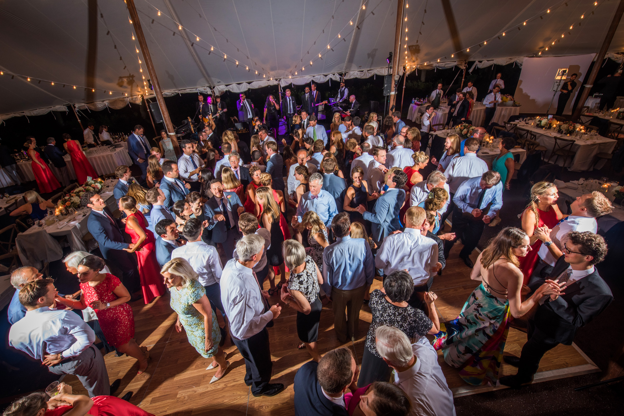 Wedding tent reception with guest dancing to live band