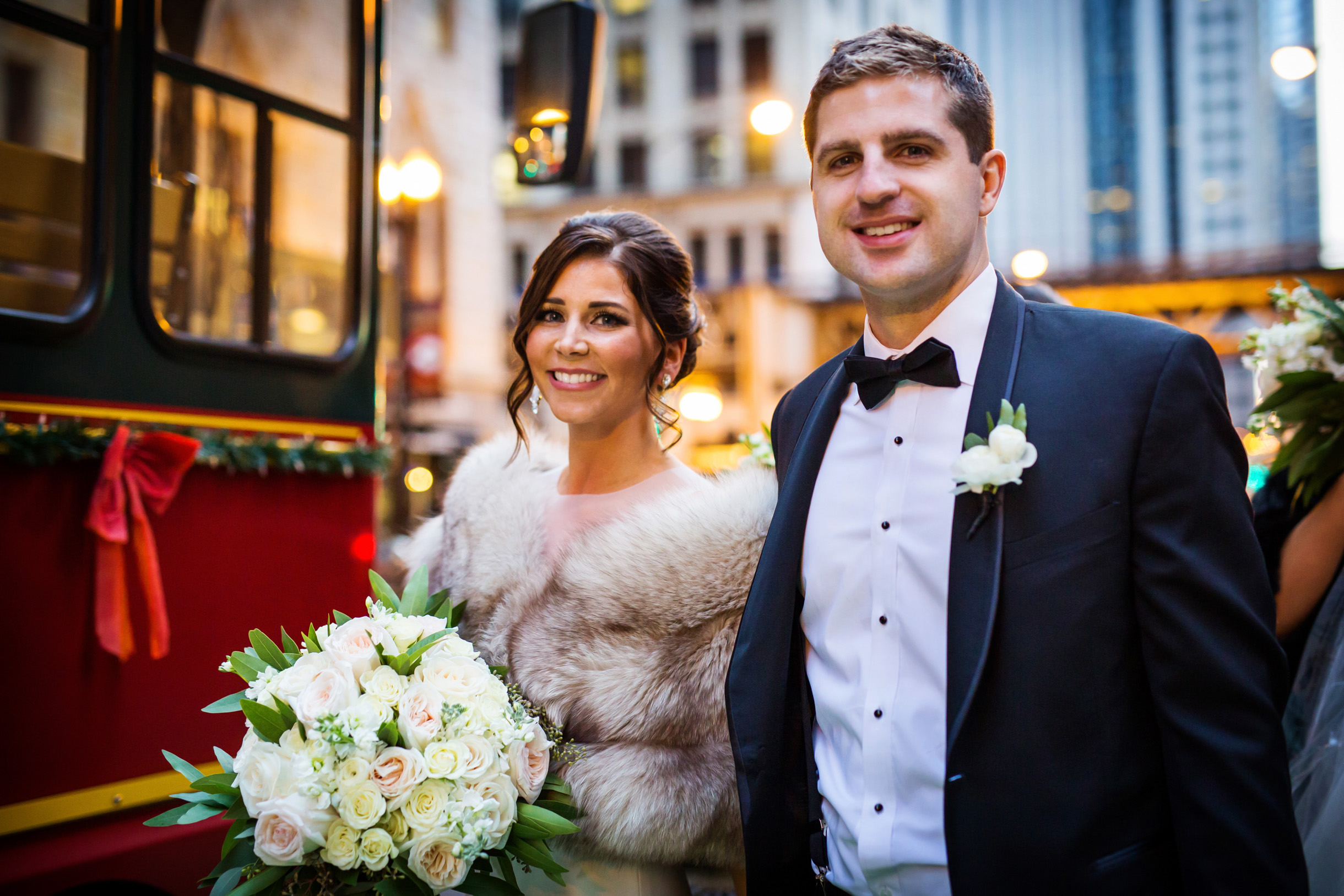 Winter wedding photo of bride and groom boarding a trolley in downtown Chicago