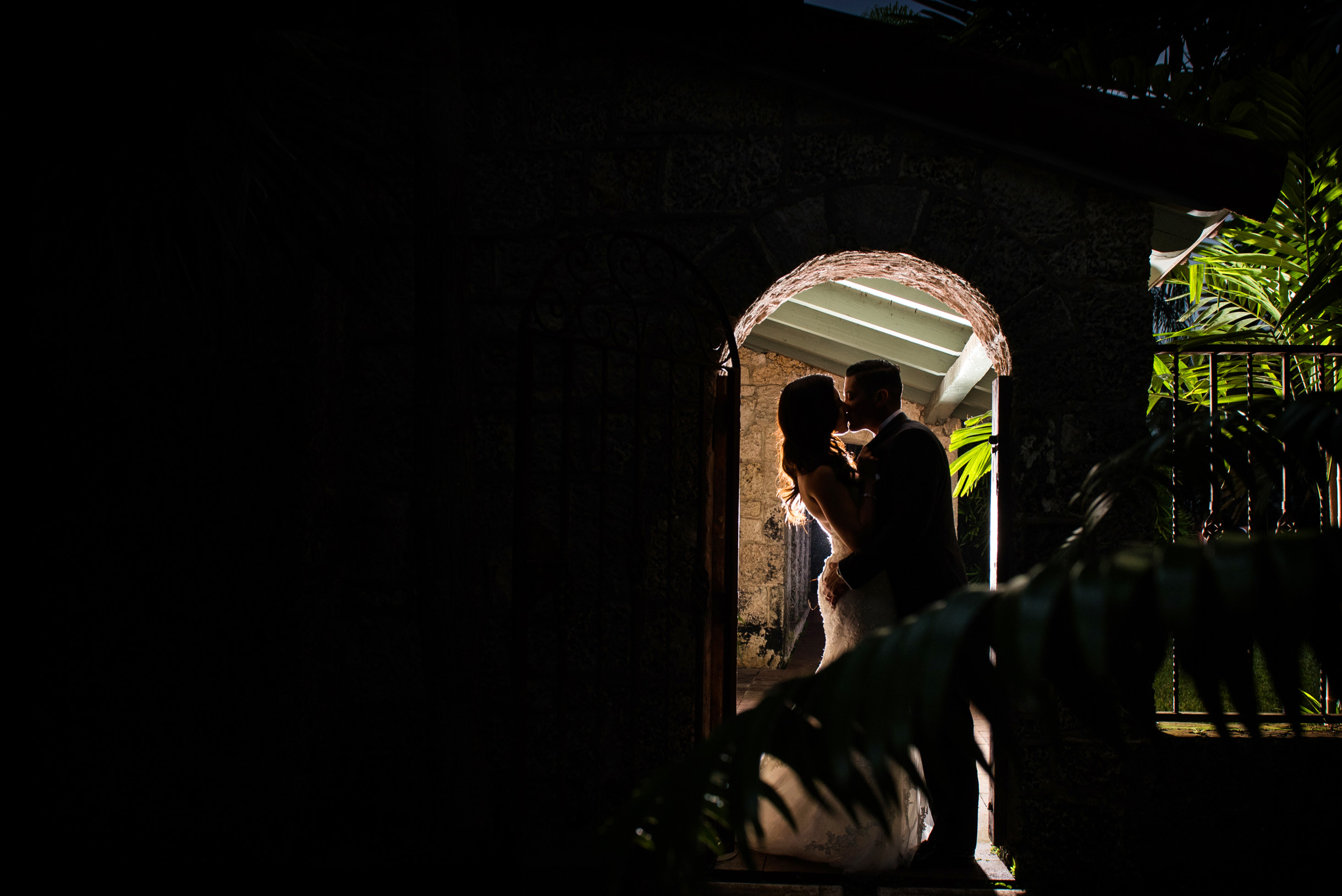 bride and groom kissing beneath spanish style roof wedding venue in south Florida near Miami at the Cooper Estate-341