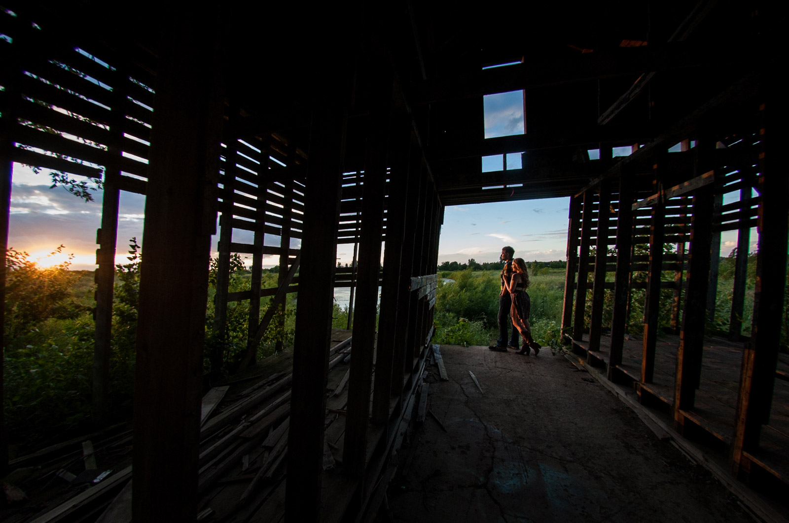 Engaged couple posing in a barn at sunset in the country