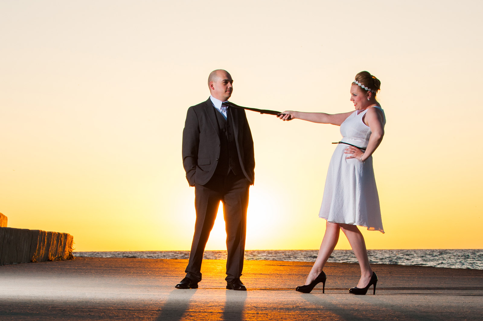 Funny enagegement session photo of bride pulling groom by his tie at sunrise along Chicago's Lake Michigan
