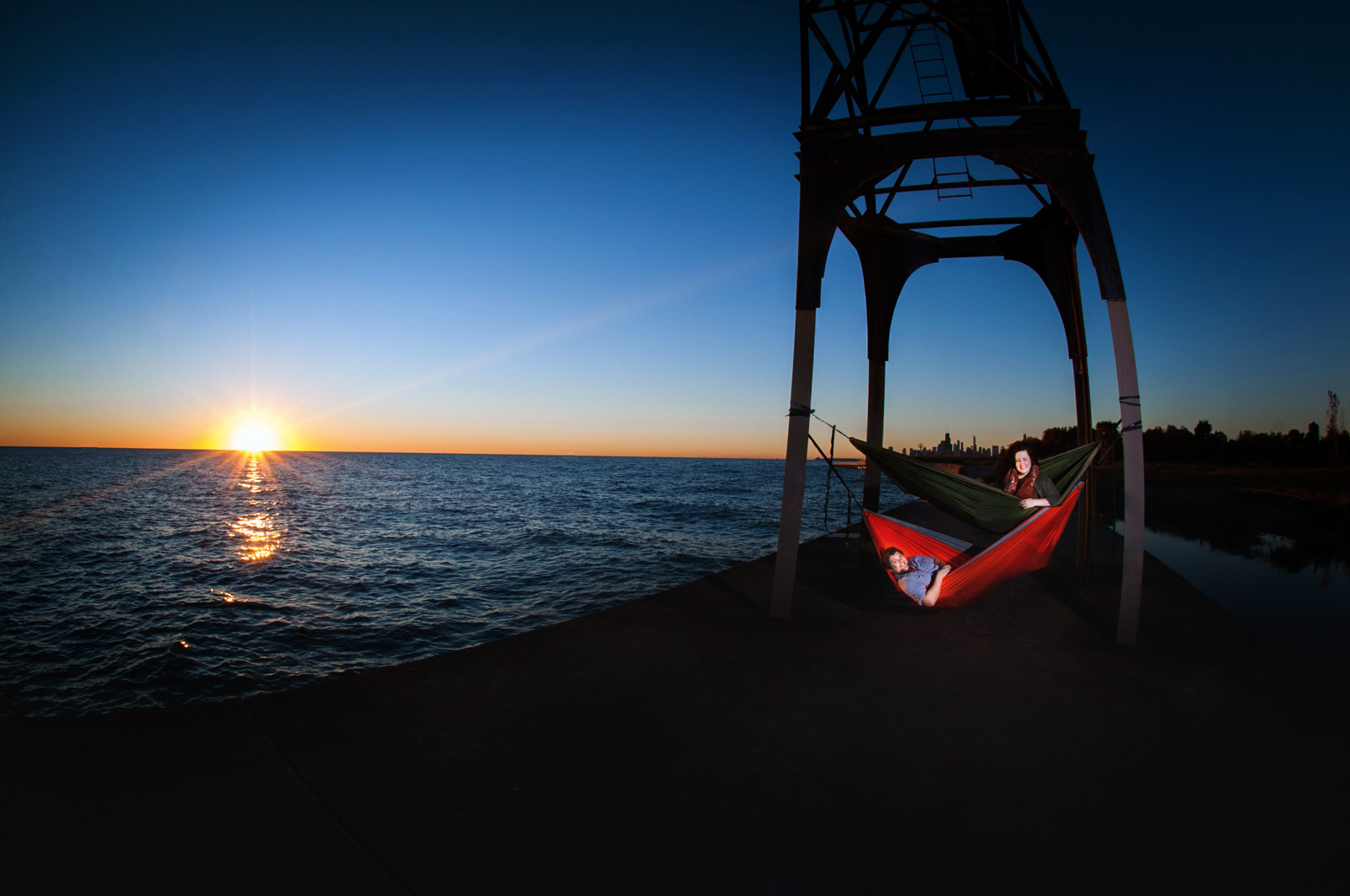 Laying in hammocks at sunrise on Lake Michigan in Chicago during their engagement session
