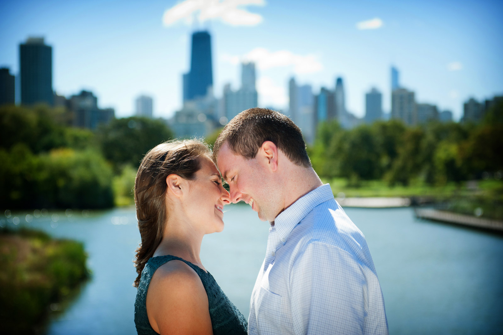 Smiling happy engagement session couple on bridge at the South Pond of Lincoln Park Zoo