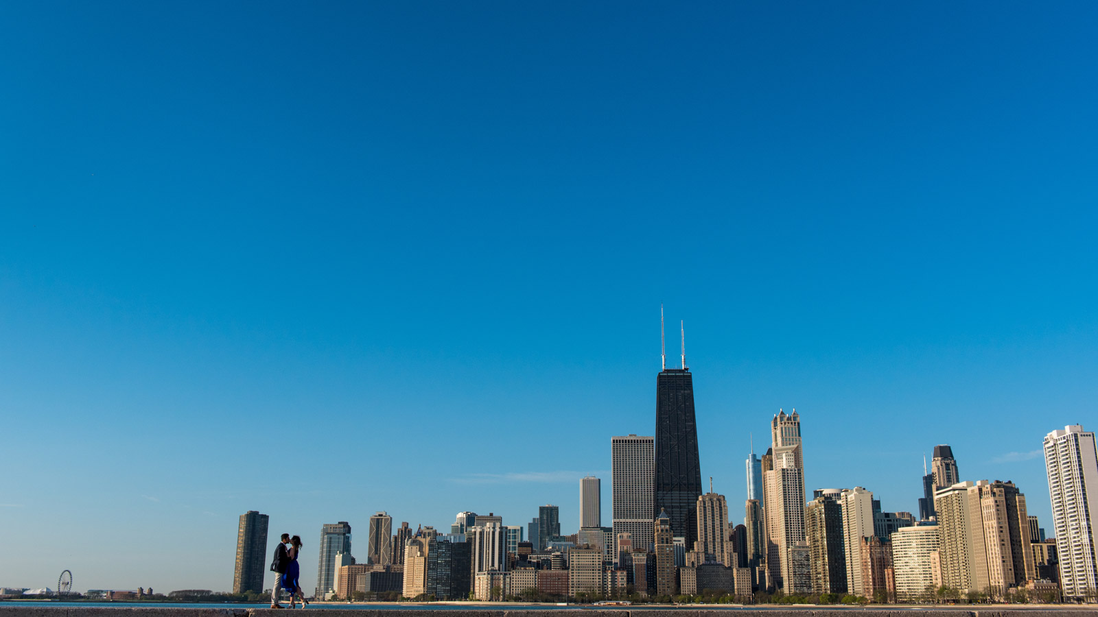 Sunrise silhouette photo of engagement session couple at North Avenue Beach in front of Chicago skyline