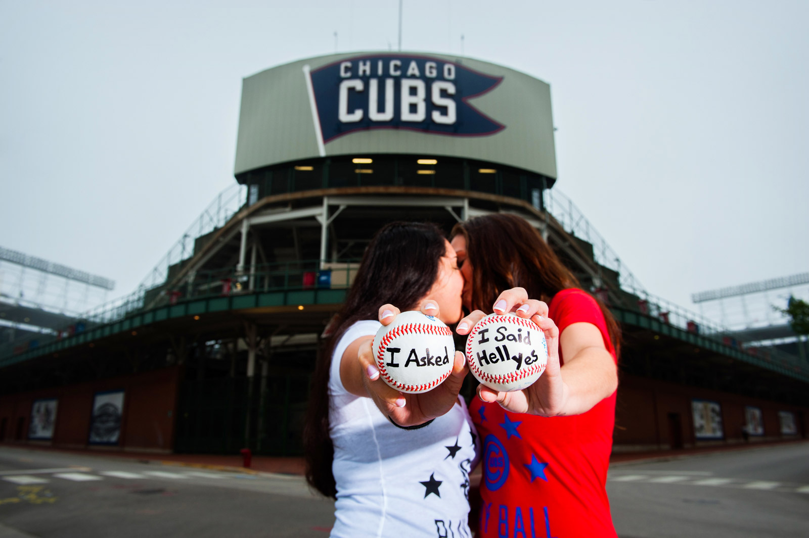same sex engagement session with baseball that says I Asked I Said Hell Yes in front of Wrigley Field in Chicago