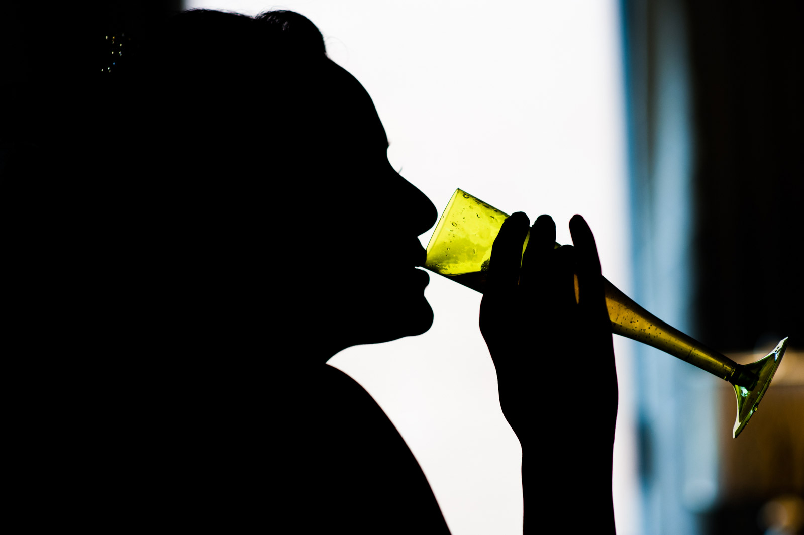 Bride in artistic silhouette drinking from champagne flute