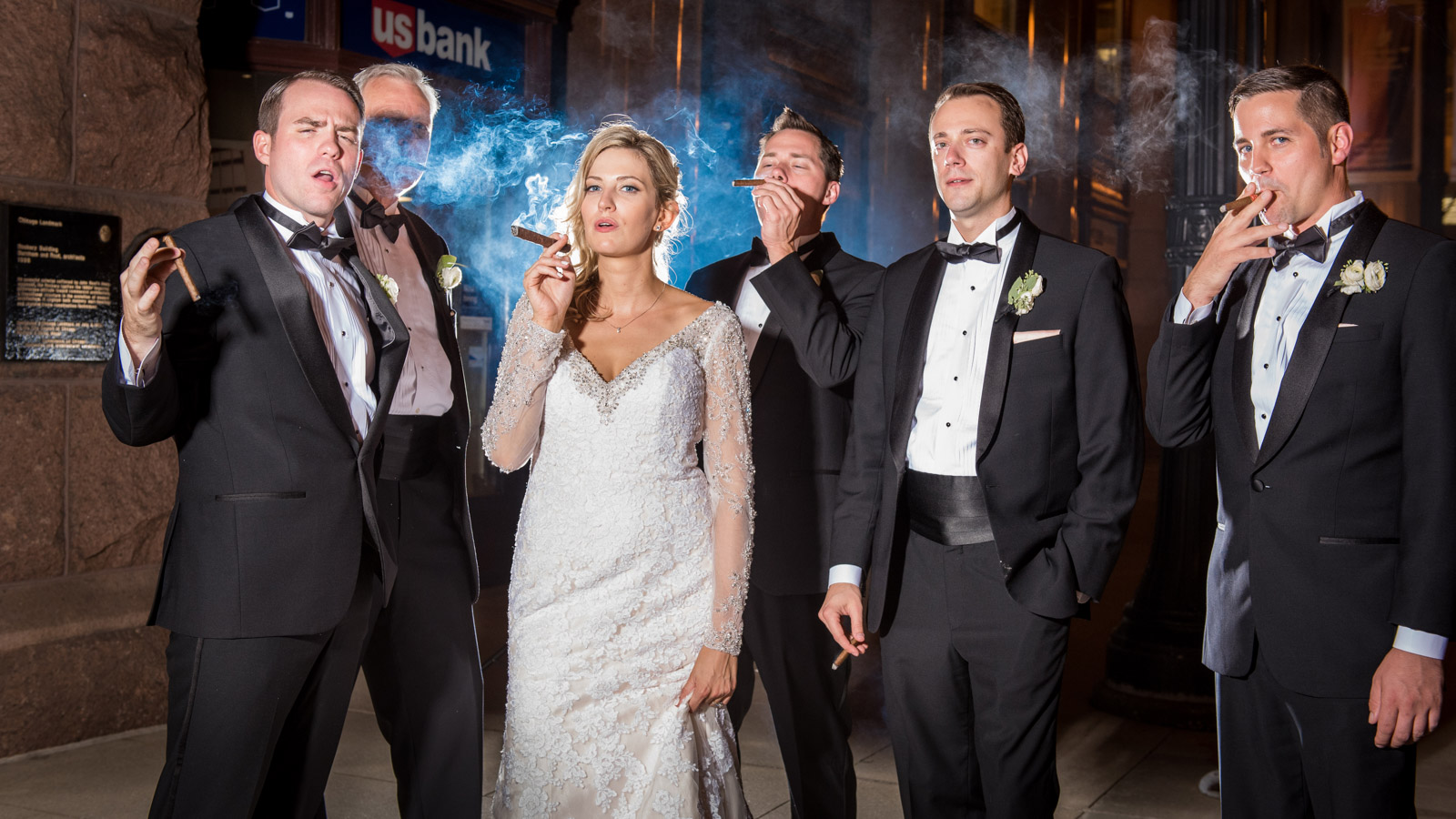 Bride smoking cigar with groomsmen on LaSalle street in Chicago in front of the Rookery