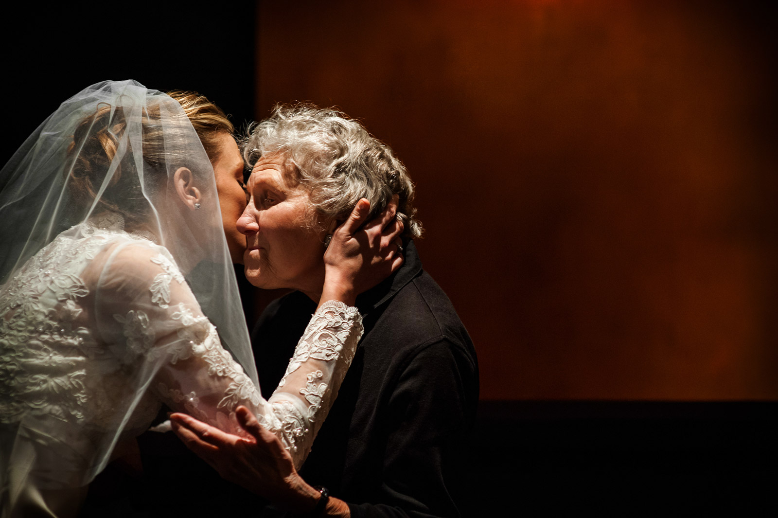 Bride wearing veil kissing grandmother